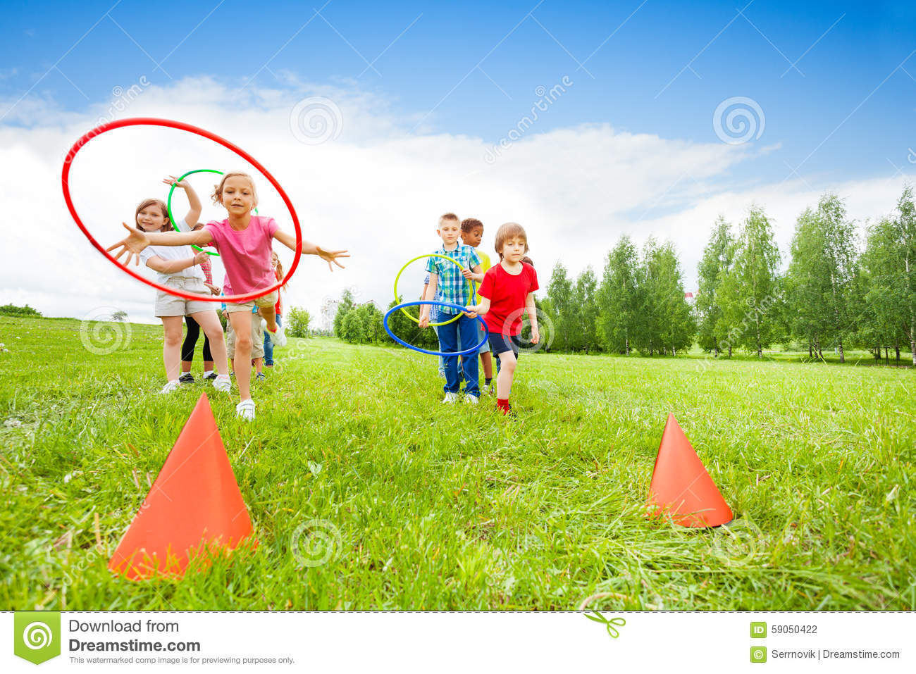 Playful Kids Throwing Colorful Hoops On Cones Stock Photo