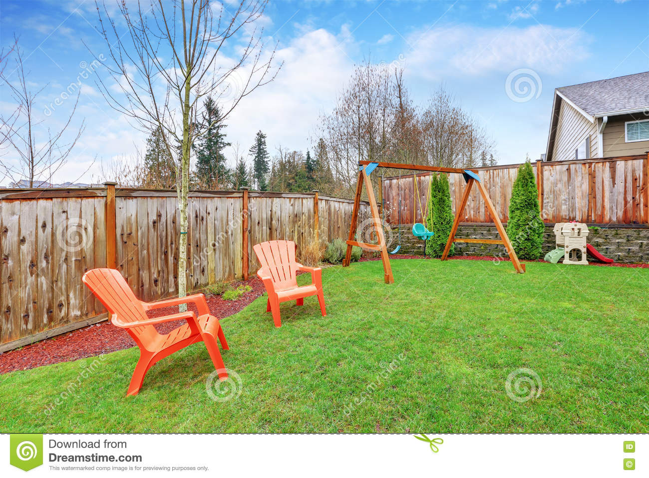 playground area in the house backyard with swings stock photo
