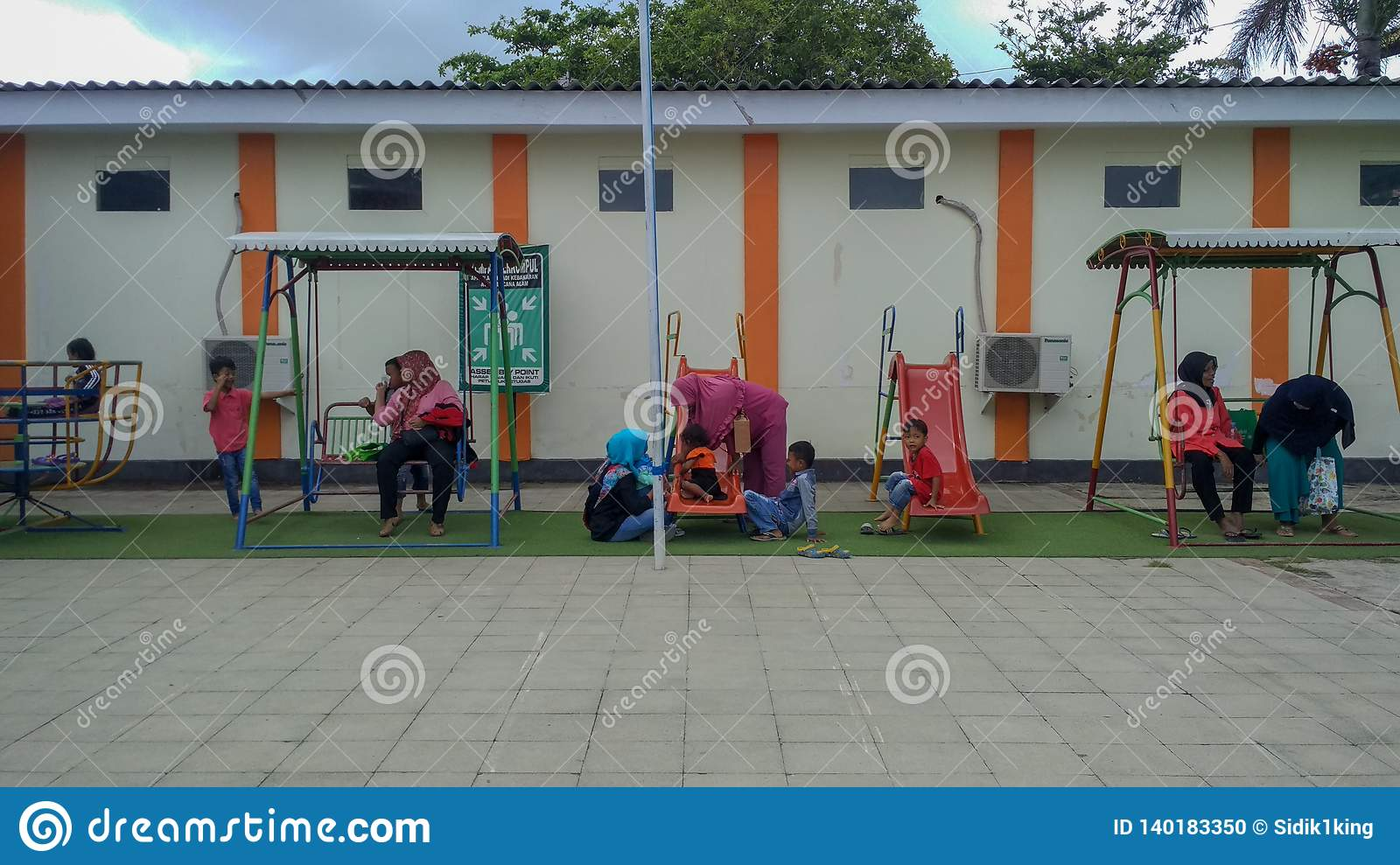 Playground in public area, childrens in sunny summer holiday.