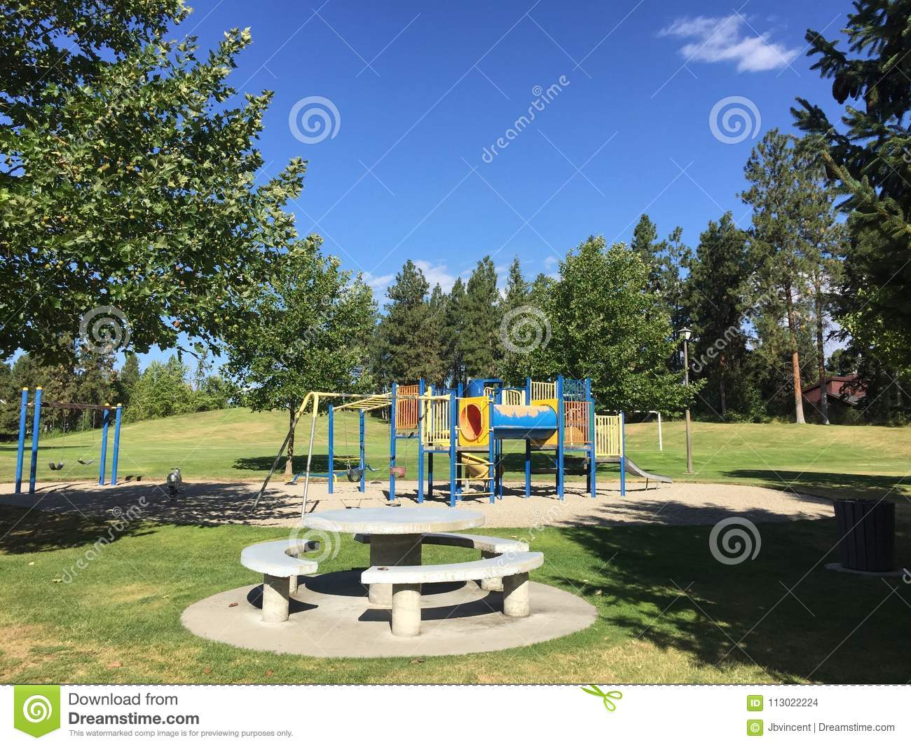 Playground And Seating Area With Trees In Summer Field Stock