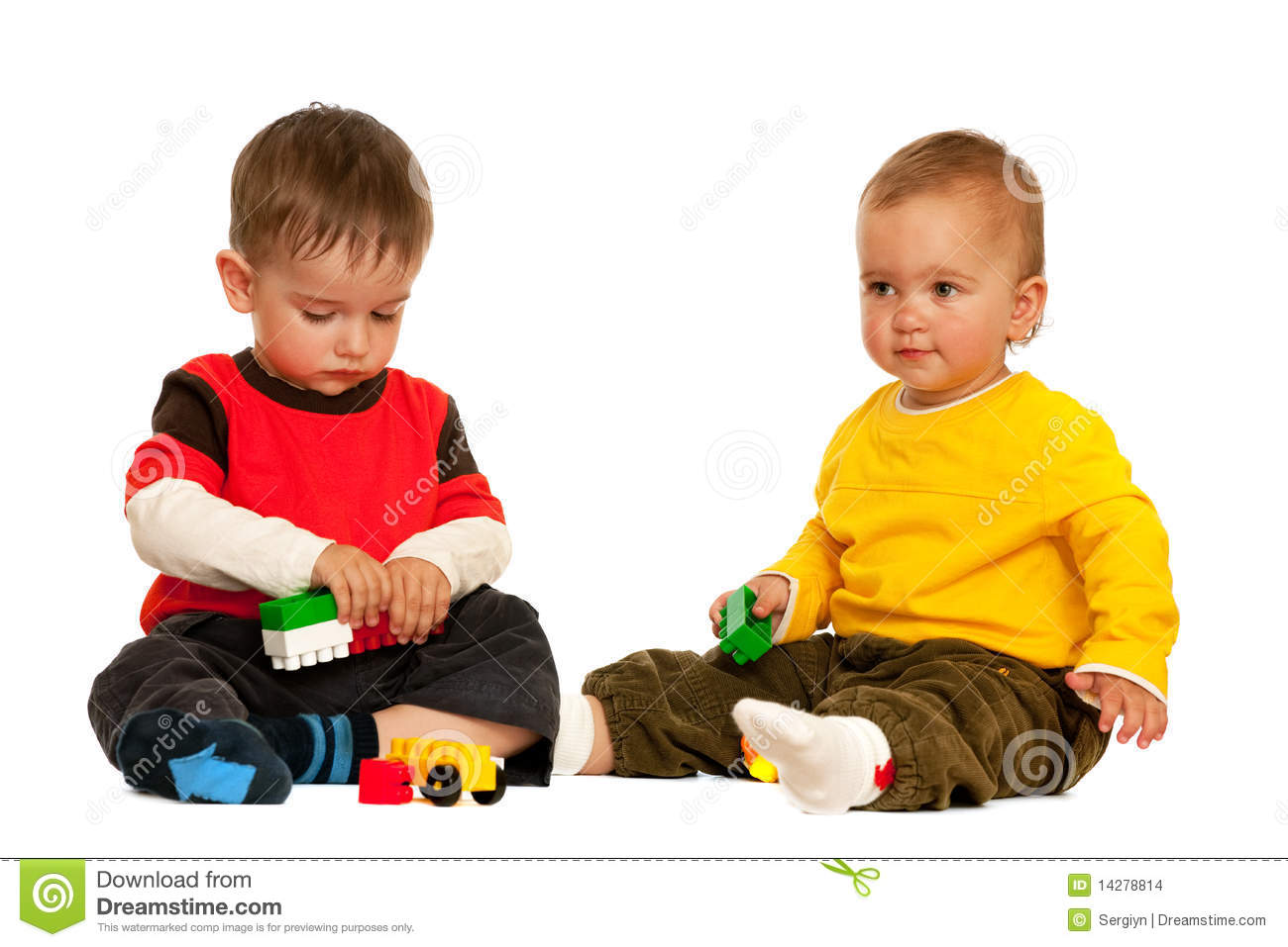 Two toddlers are playing with blocks; isolated on the white background ...