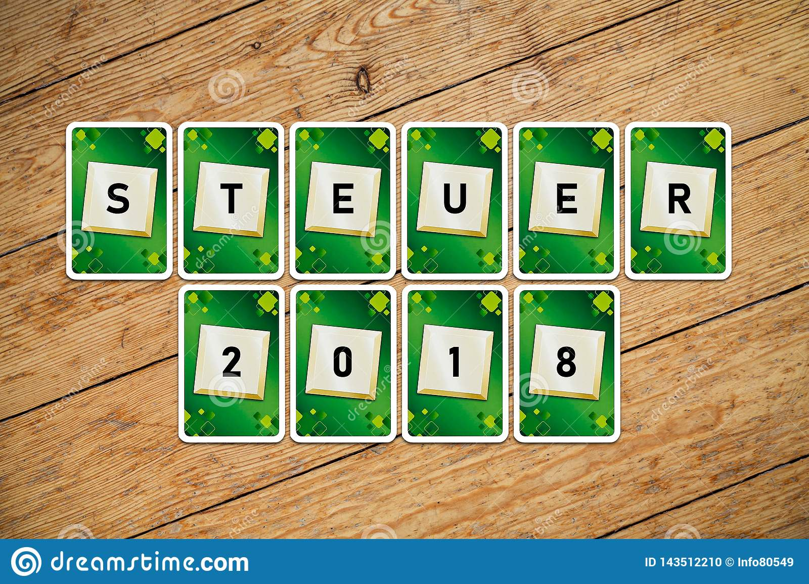 Playing cards with text `Steuer 2018` on a wooden floor