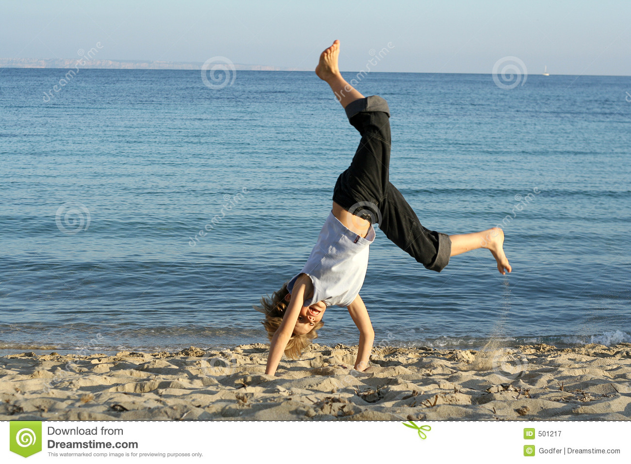 playing handstand beach