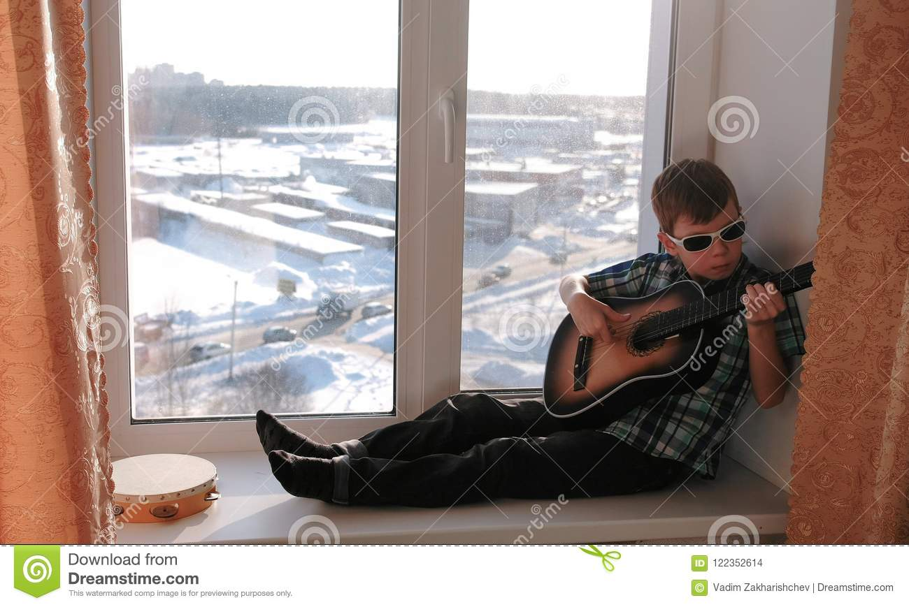Playing a musical instrument. Boy in sunglasses plays the guitar sitting on the windowsill.