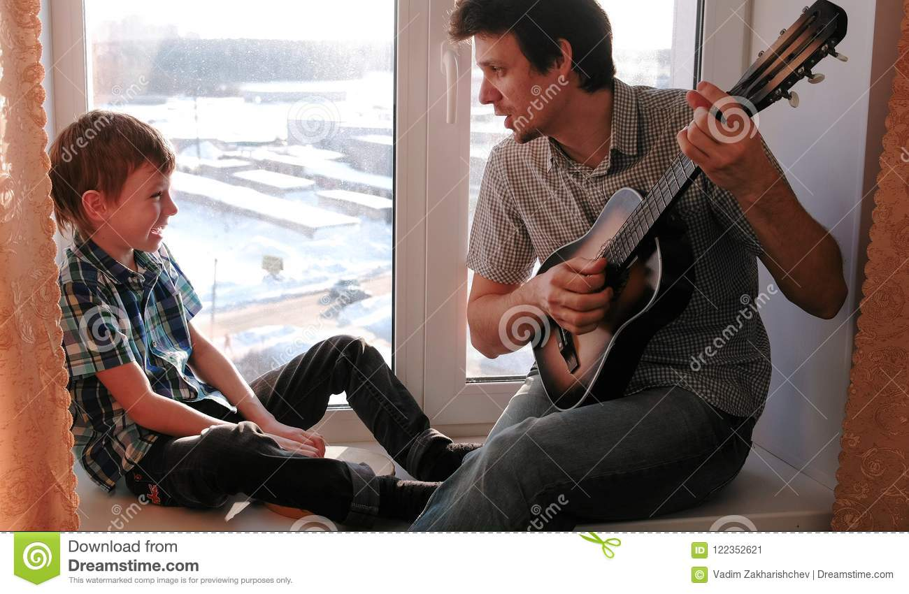 Playing a musical instrument. Dad is playing the guitar and son is playing tambourine sitting in windowsill.