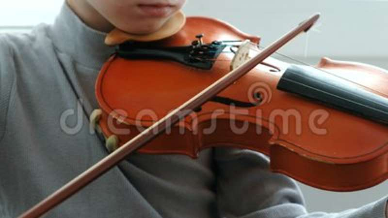 Playing the violin  Unrecognizable seven years old boy playing the violin  closeup  Front view