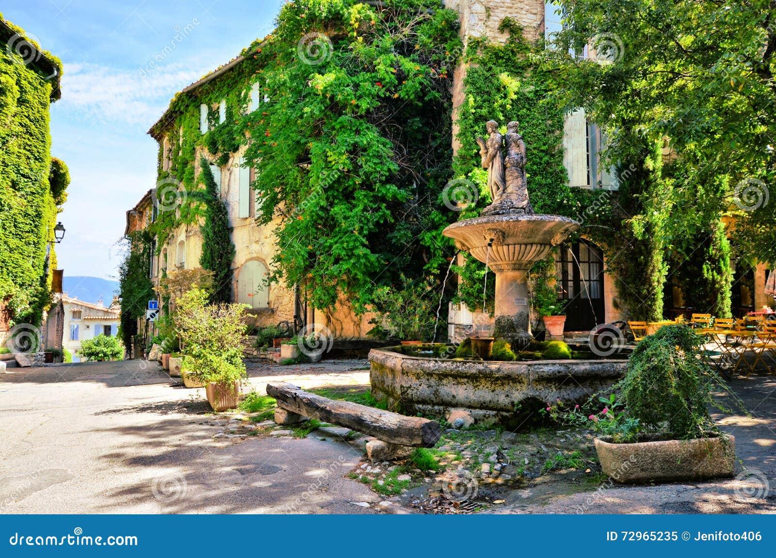 Plaza frondosa con la fuente, Provence, Francia