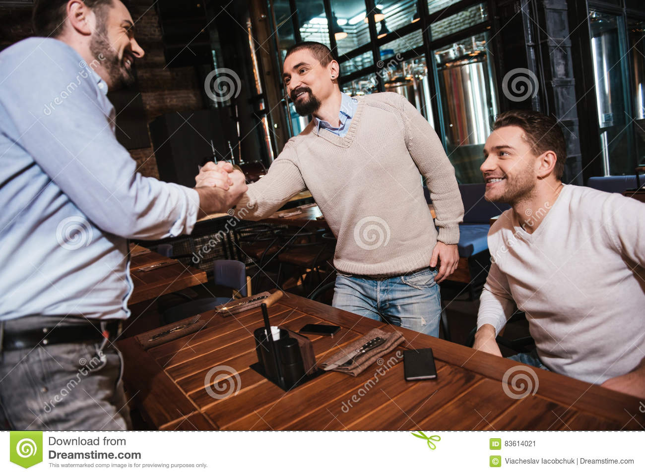 Pleasant bearded man greeting his friend stock image image of menu pleasant bearded positive men standing opposite his friend and shaking his hand while greeting him m4hsunfo