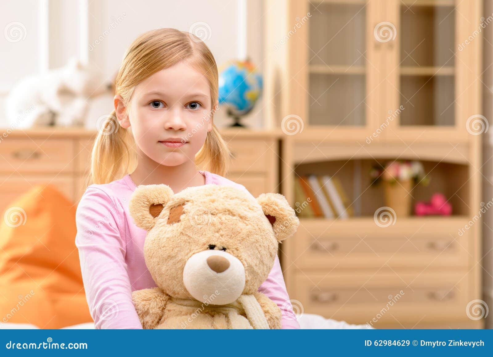 Pleasant girl holding bear