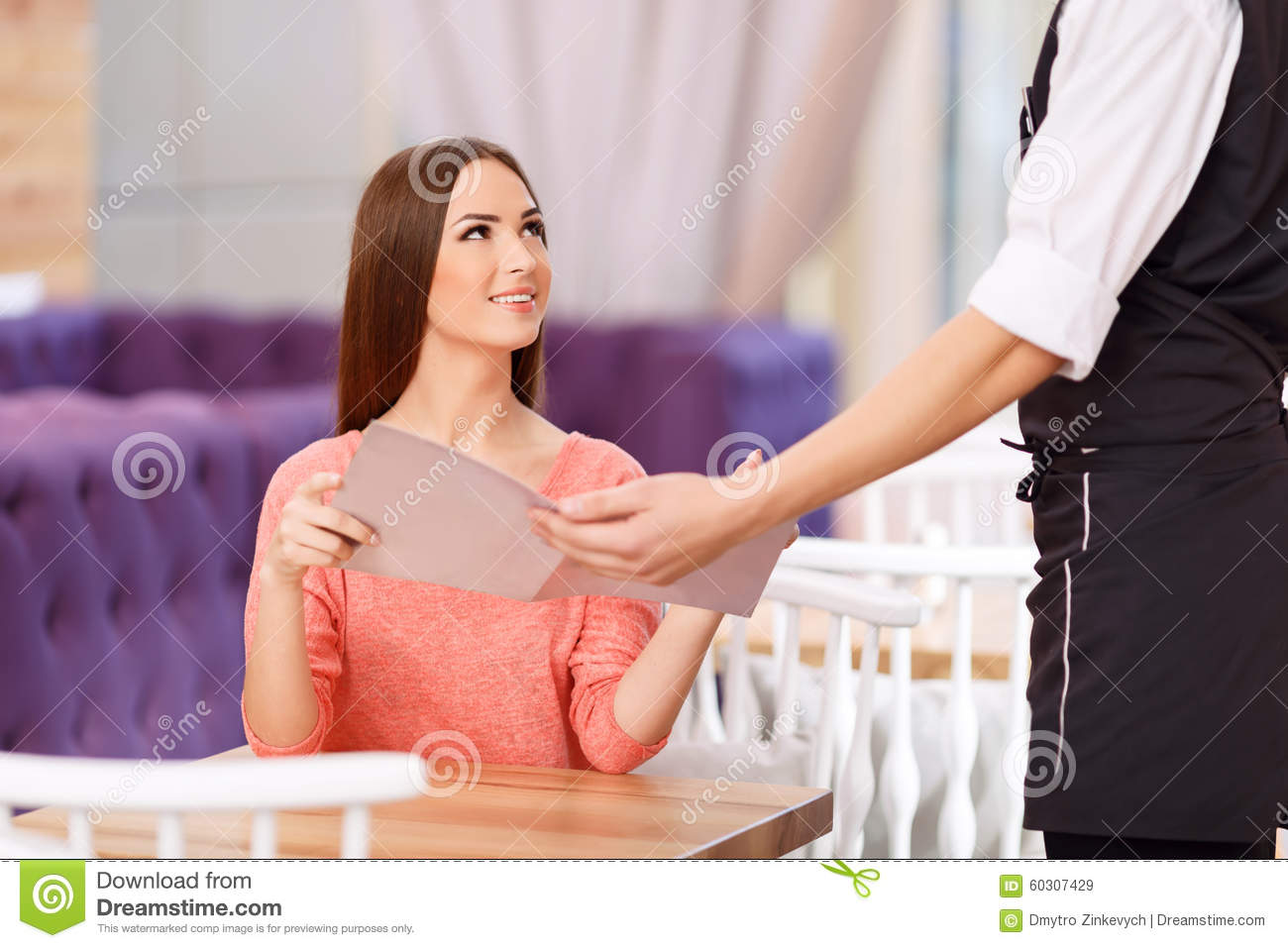 Appealing girl sitting at the table and getting menu from the waiter