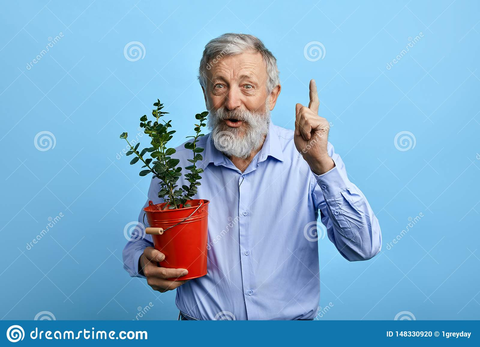 Pleasant happy man pointing up while holding a busket with flower.