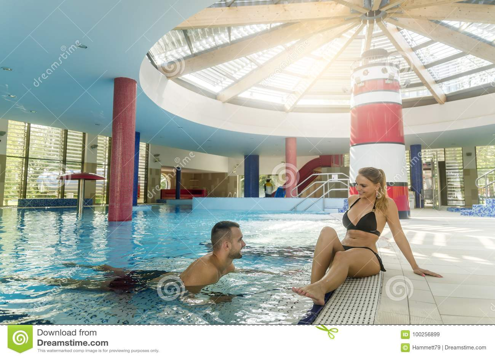 Pleasant loving couple resting near swimming pool