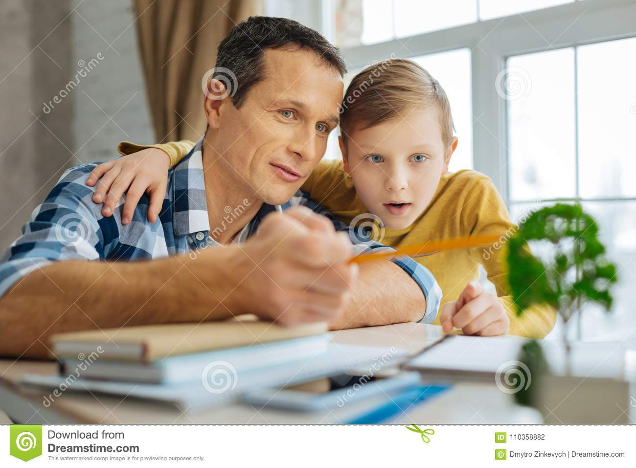 Pleasant young men and his pre-teen son bonding to each other in the fathers  office while the men telling the boy about the benefit of trees for the ...