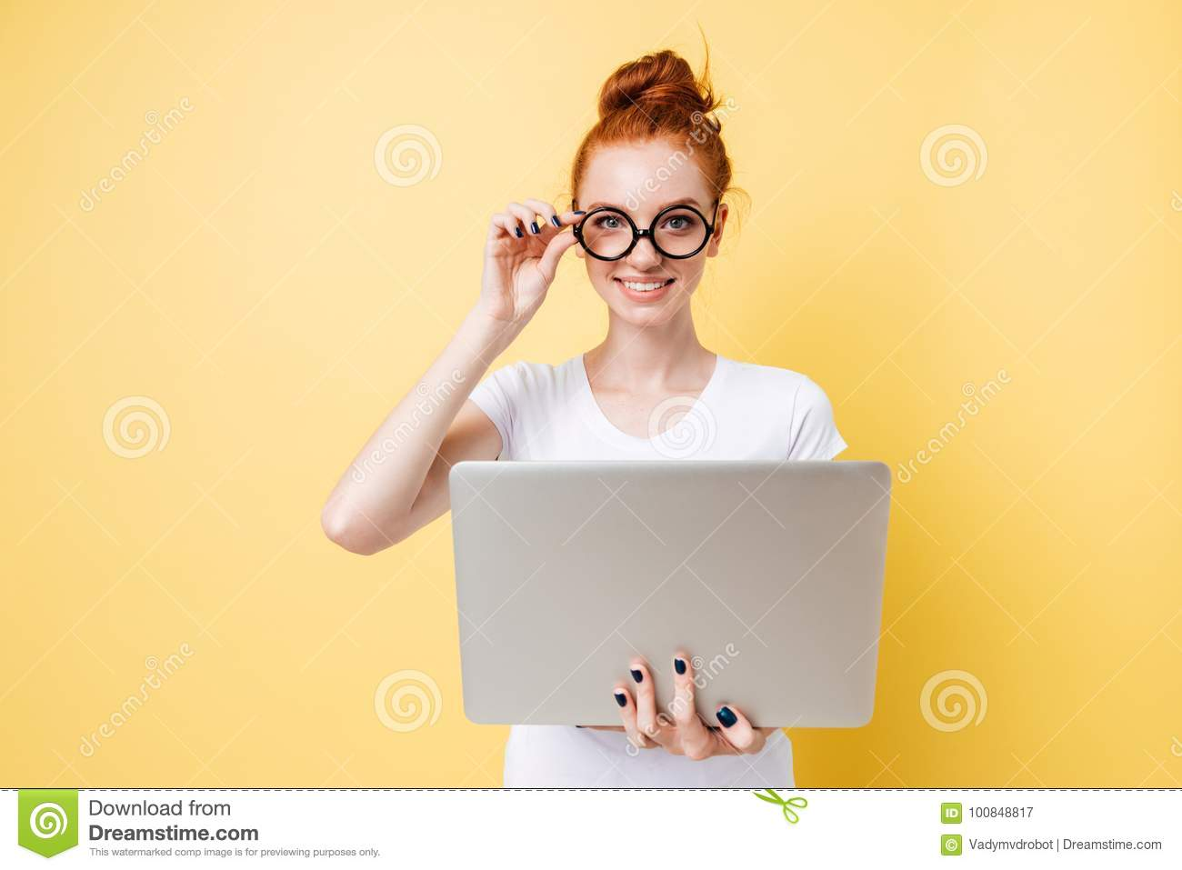 Pleased ginger woman in eeglasses holding laptop computer