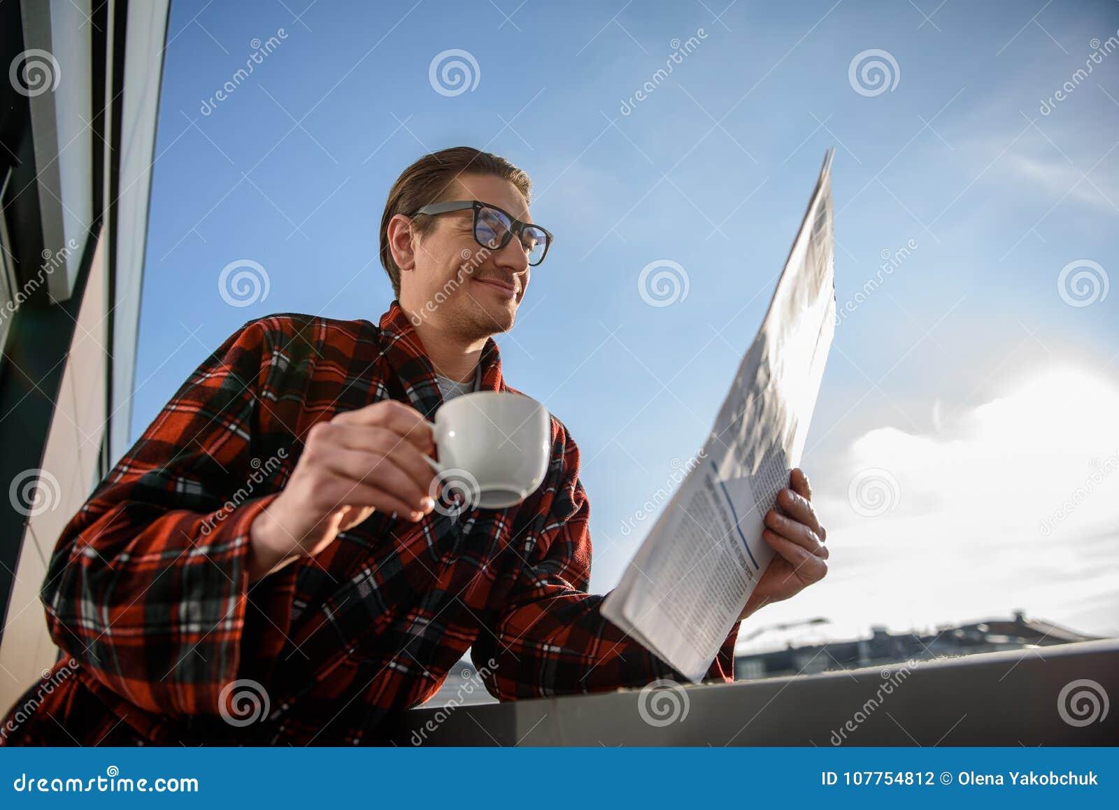 Pleased man enjoying coffee and journal on terrace