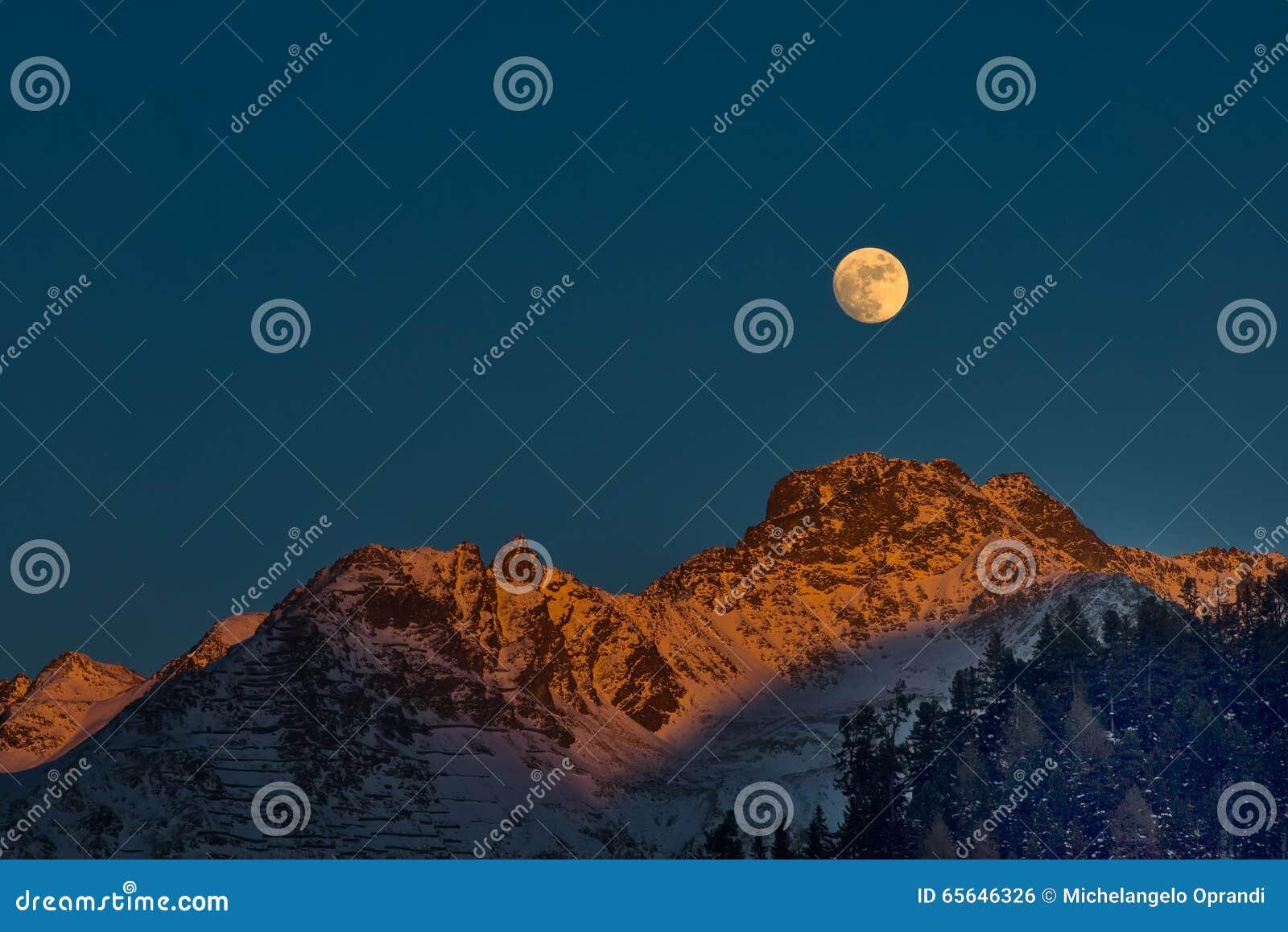 Pleine lune au coucher du soleil sur des montagnes d hiver