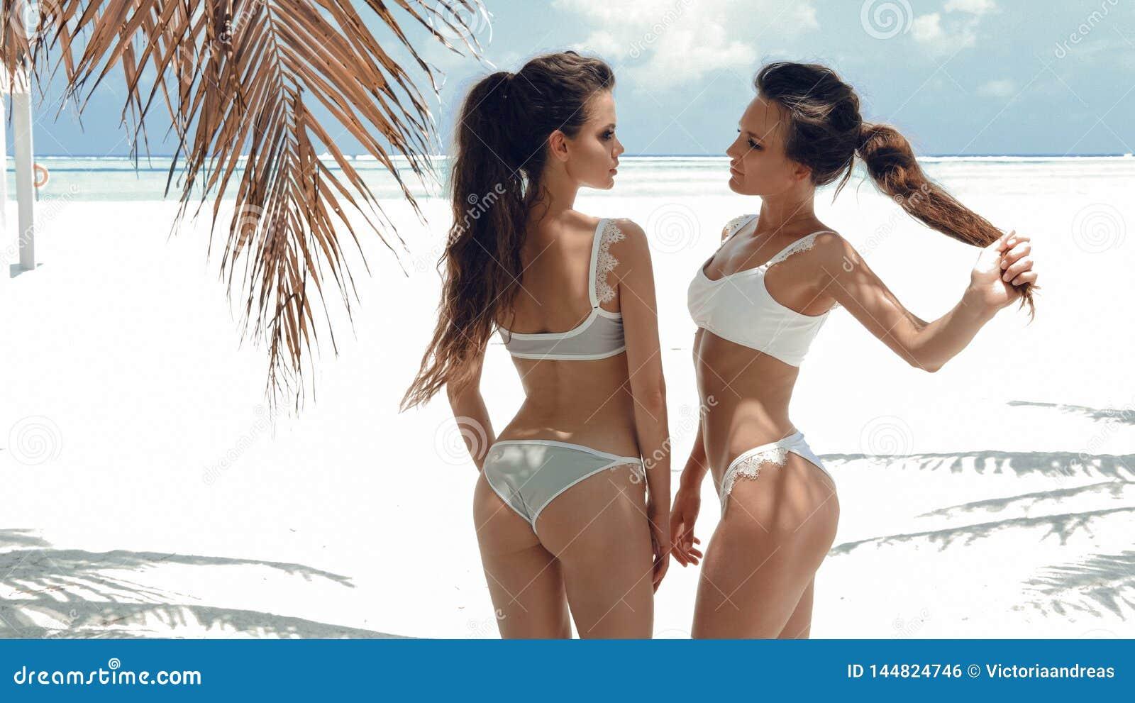Plenerowa fotografia dwa seksownej bikini dziewczyny modeluje w mod swimsuits na tropikalnej plaży przy Maldives wyspą Szczupł