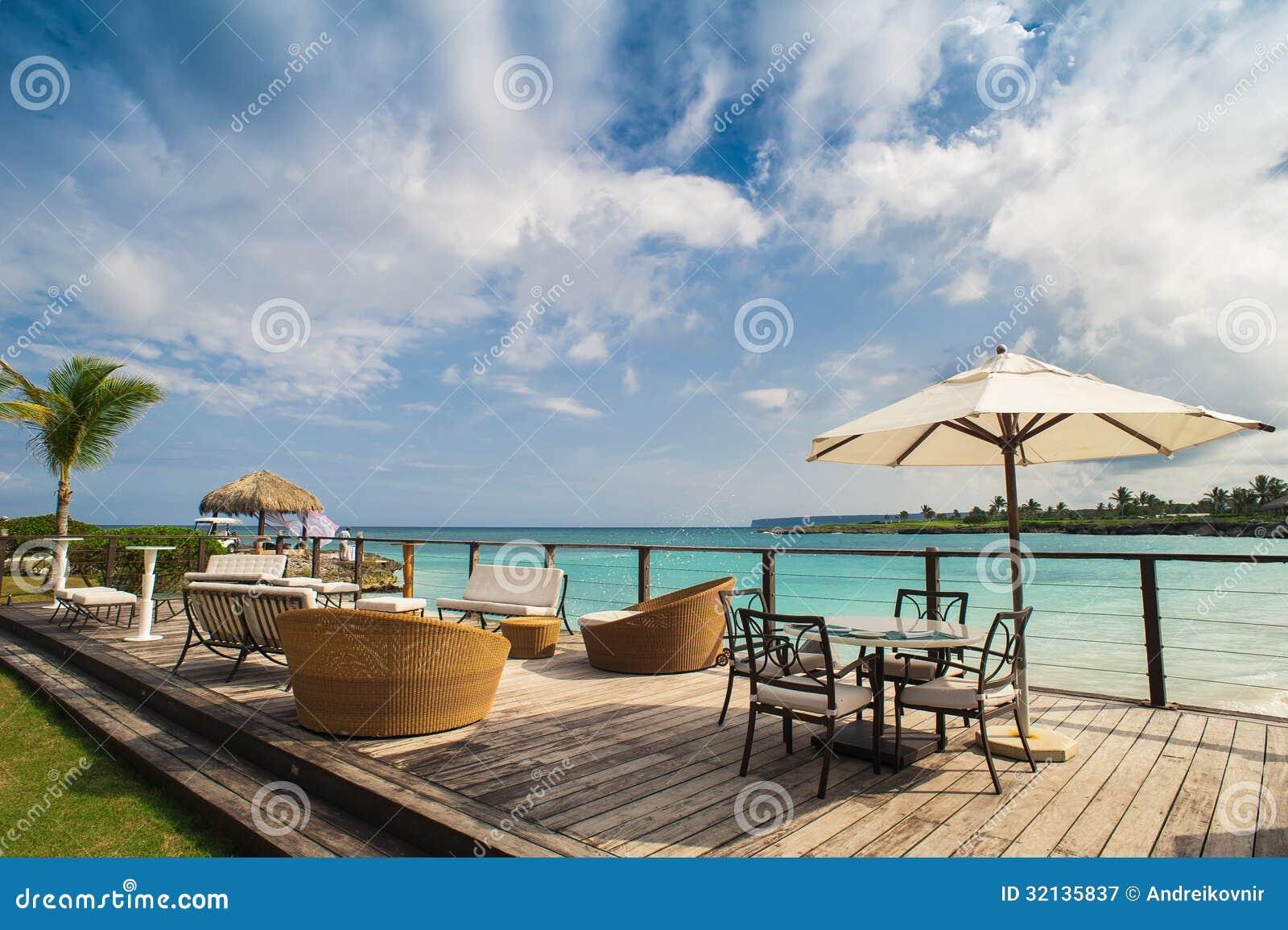 Plenerowa restauracja przy plażą. Kawiarnia na plaży, oceanie i niebie. Stołowy położenie przy tropikalną plażową restauracją. Rep
