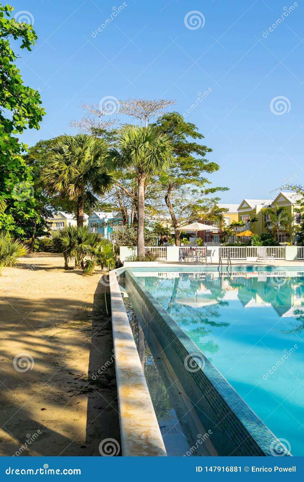Plenerowy basen na białej piasek plaży własności nowożytny mieszkaniowy sąsiedztwo z kolorowymi grodzkimi domami, domami/