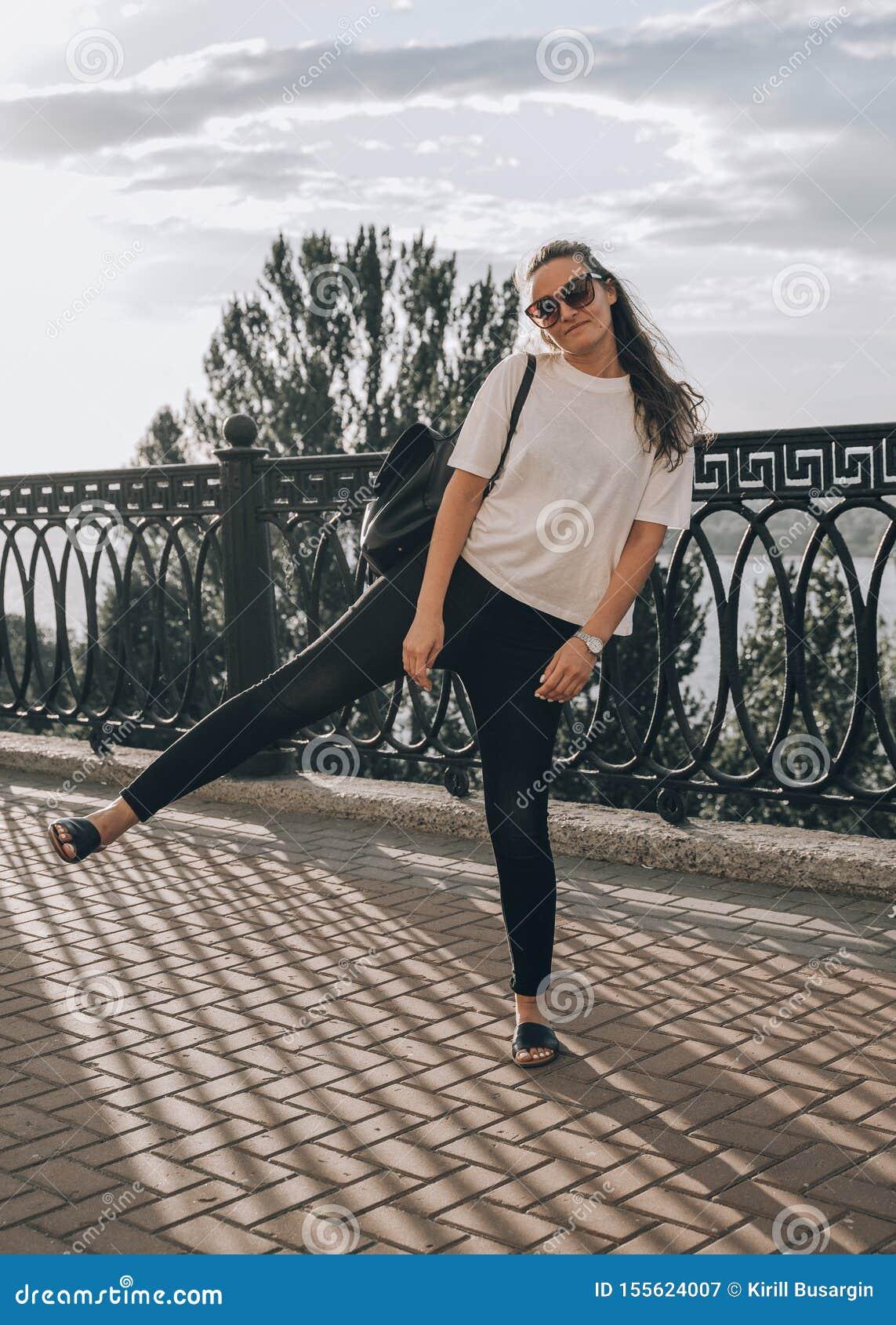 Plenerowy lata styl życia wizerunek młoda ładna modniś kobieta ma zabawę, słuchającą muzykę i tana na ulicie, centrum miasta