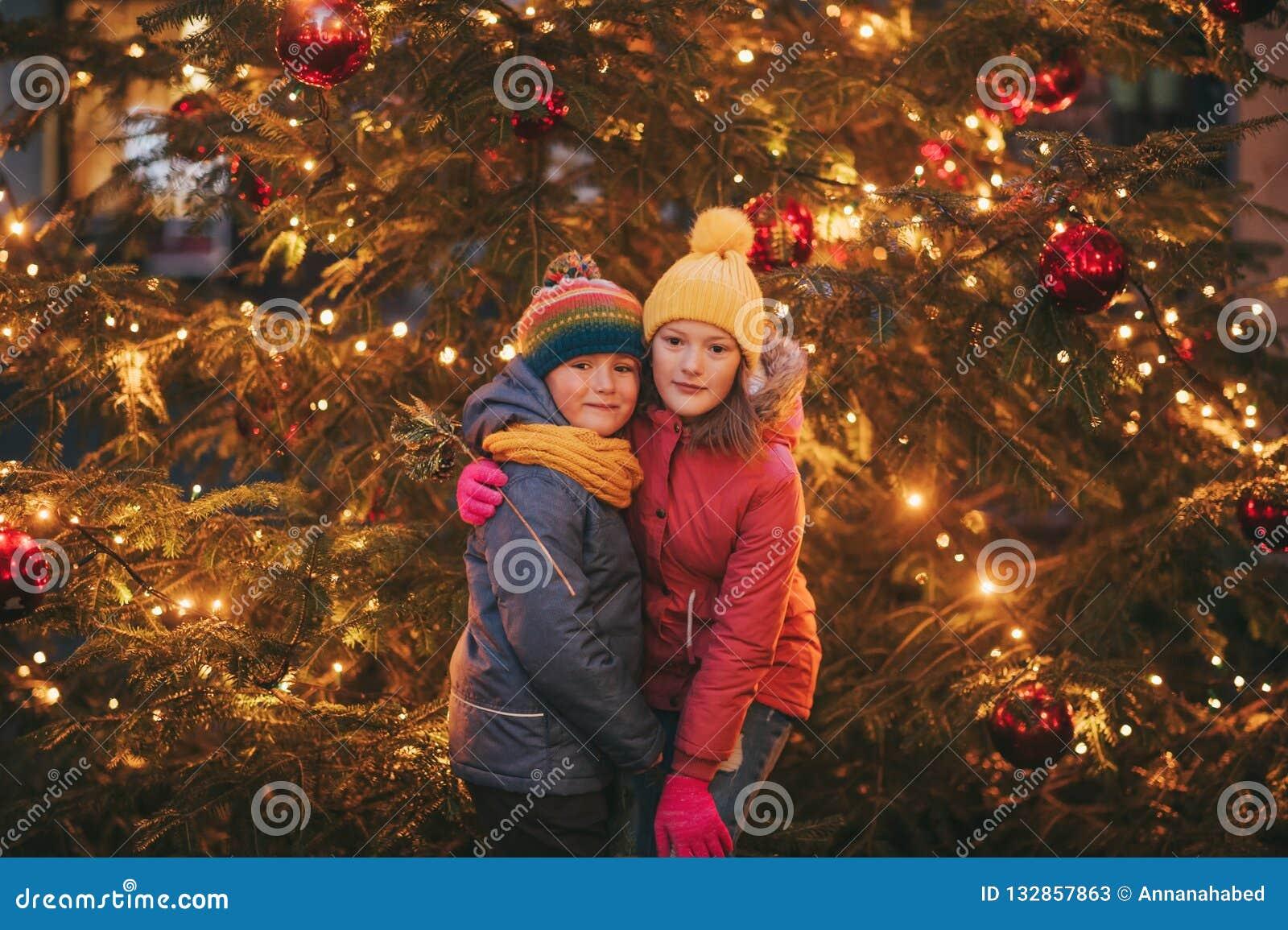 Plenerowy portret małe dzieci obok choinki z światłami
