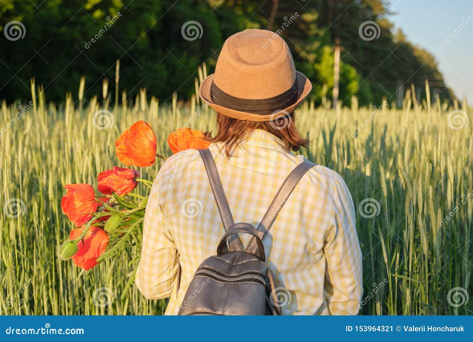 Plenerowy portret szczęśliwa dojrzała kobieta z bukietami czerwoni maczki kwitnie