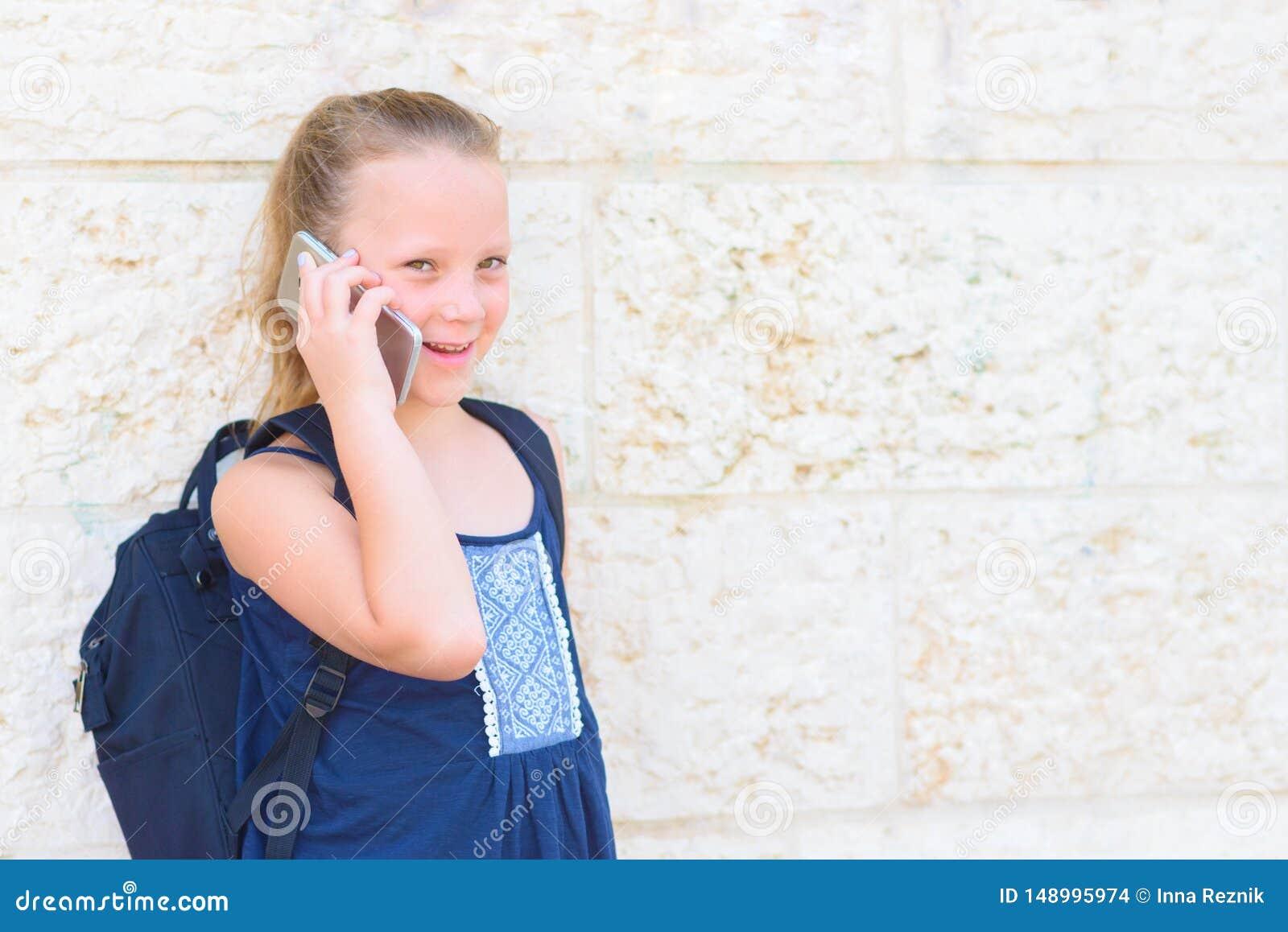Plenerowy portret szcz??liwy dziewczyny 8-9 roczniak opowiada na telefonie