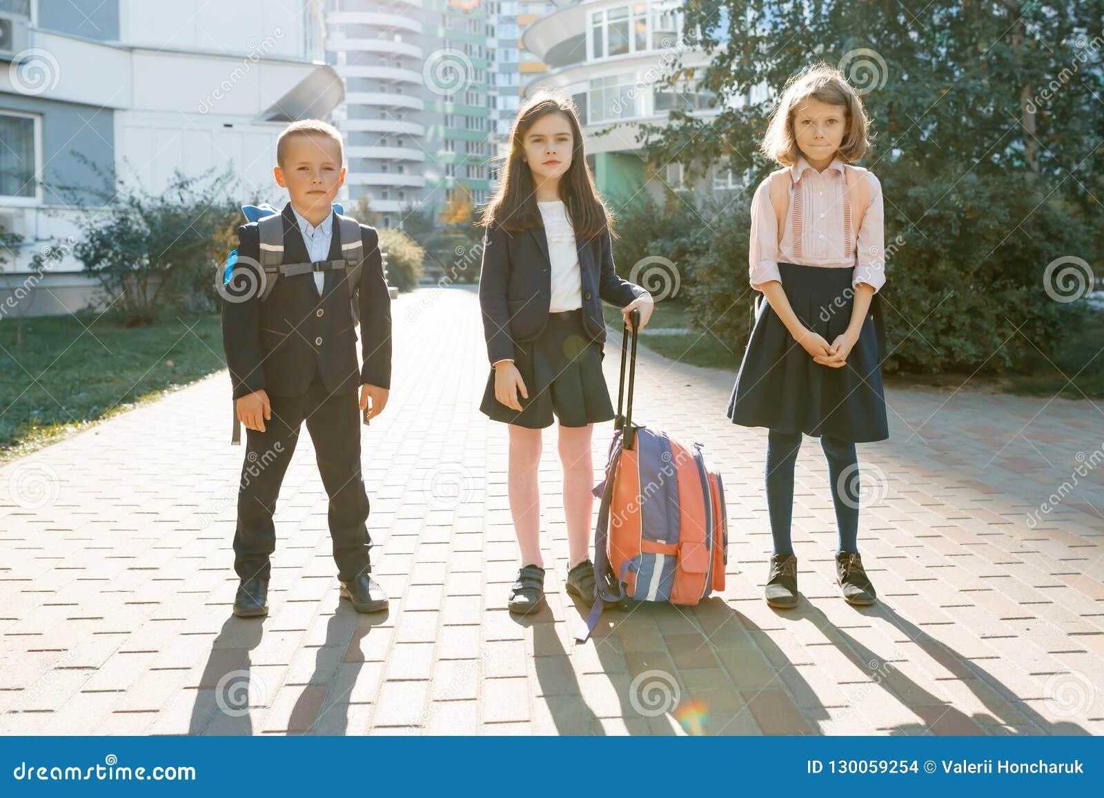 Plenerowy portret uśmiechnięci ucznie w szkole podstawowej Grupa dzieciaki z plecakami ma zabawę, opowiada Edukacja