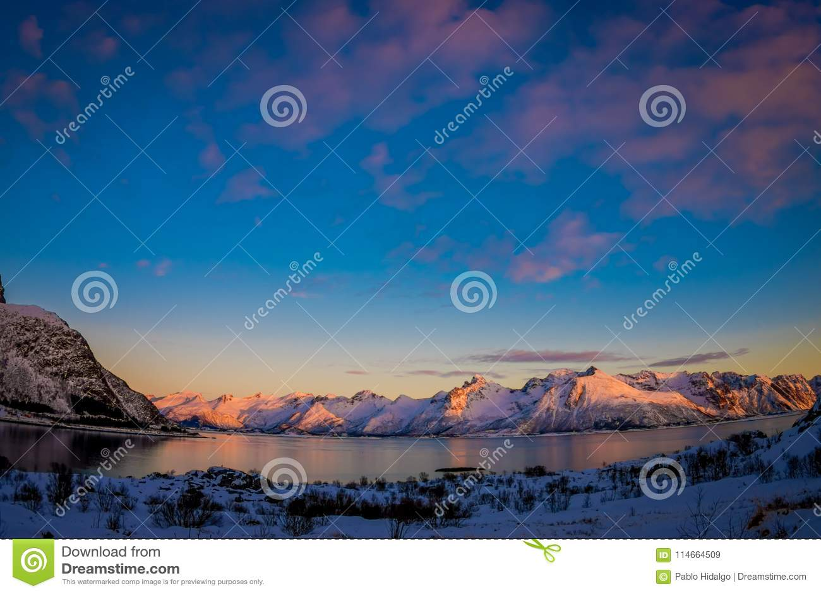 Plenerowy widok wspaniały zmierzch nad halnymi szczytami coevered z śnieżnym i częściowym marznącym jeziorem w Svolvaer