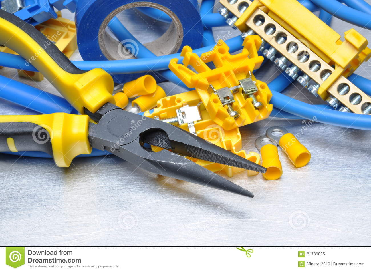Pliers with electrical component kit on grey metal background