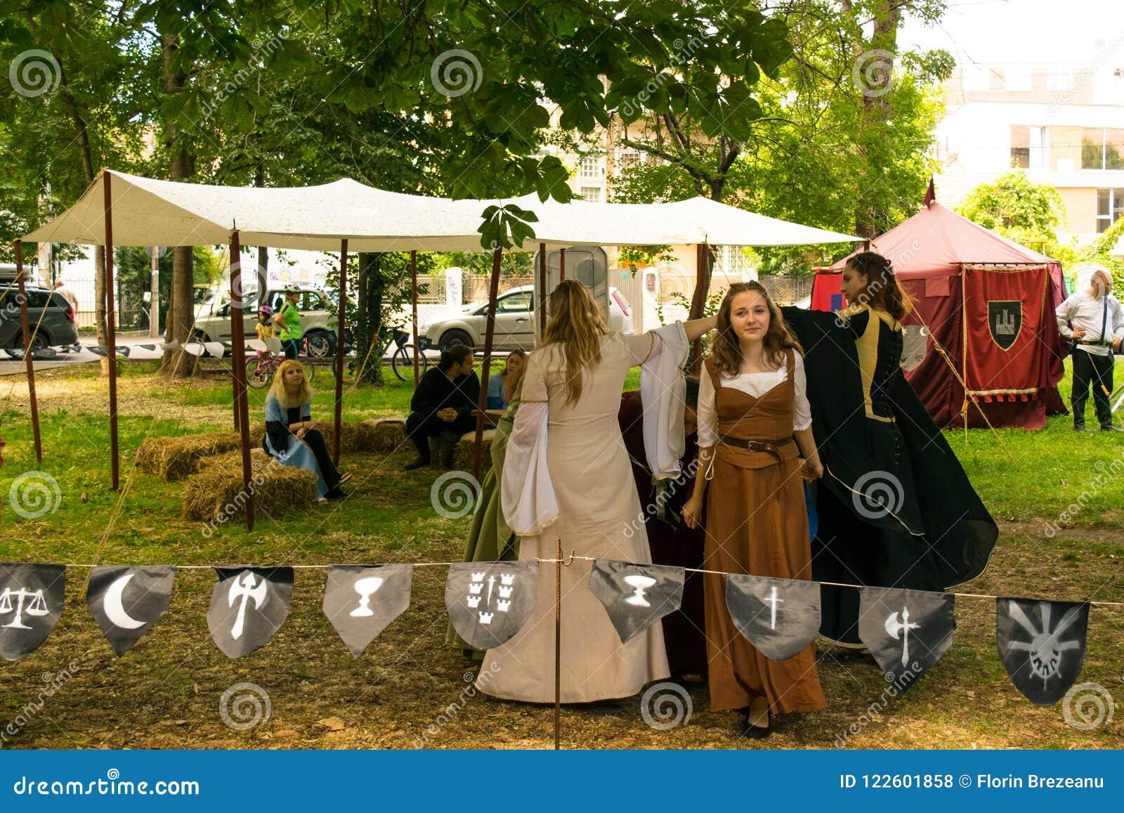 Ploiesti, Roemenië - Juli 14, 2018: De geklede omhoog dames reproduceren oude middeleeuwse dans in openluchtscène bij Middeleeuws