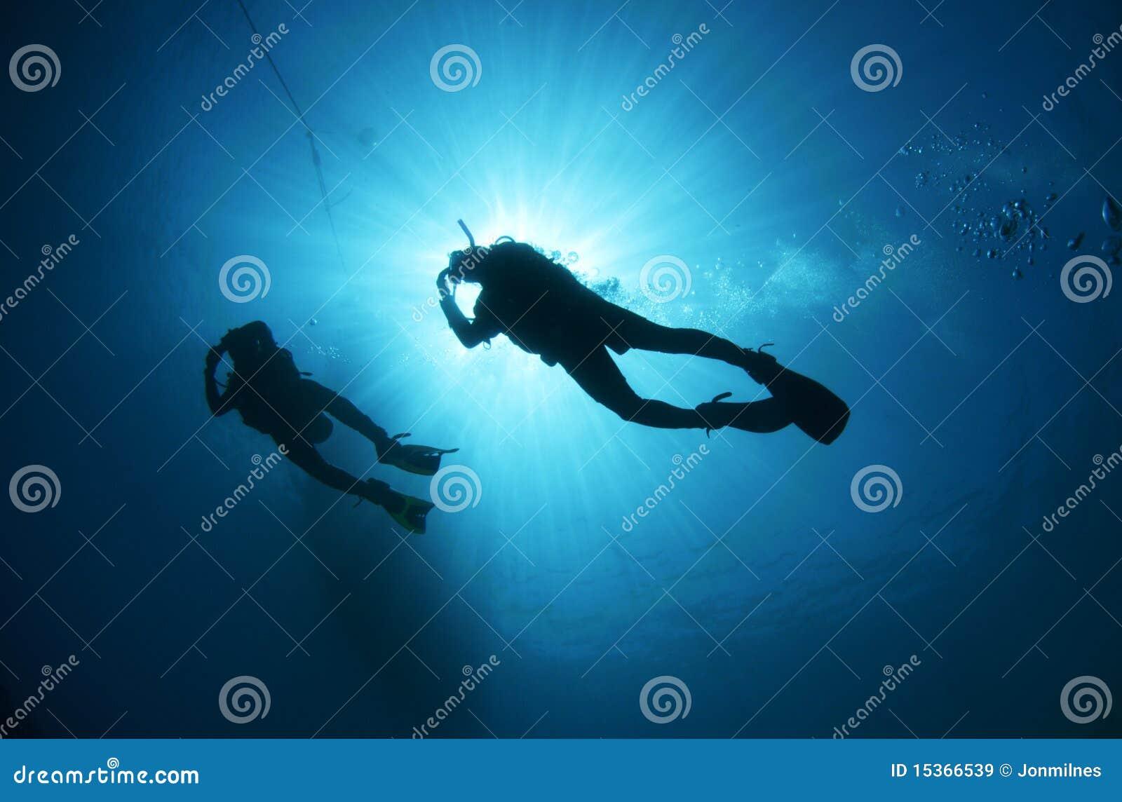Plongeur autonome silhouetté contre le soleil
