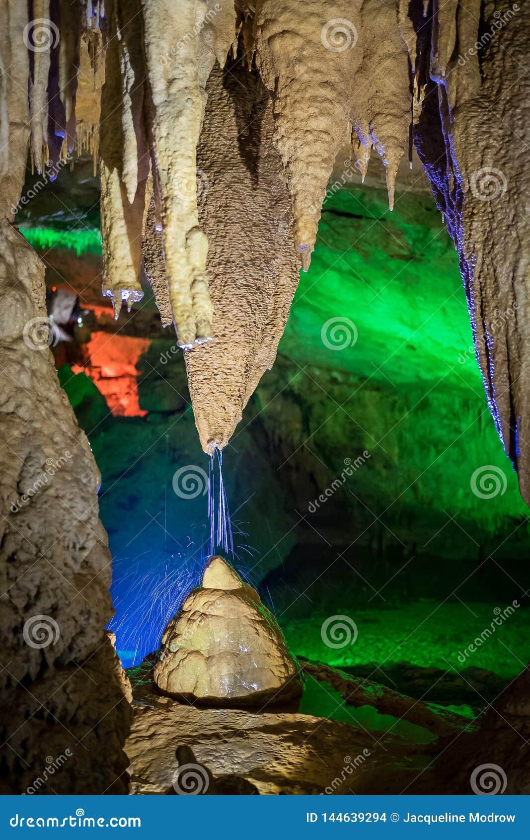 Plonsen van water van een stalactiet die tot een stalagmiet onder het in een hol leiden
