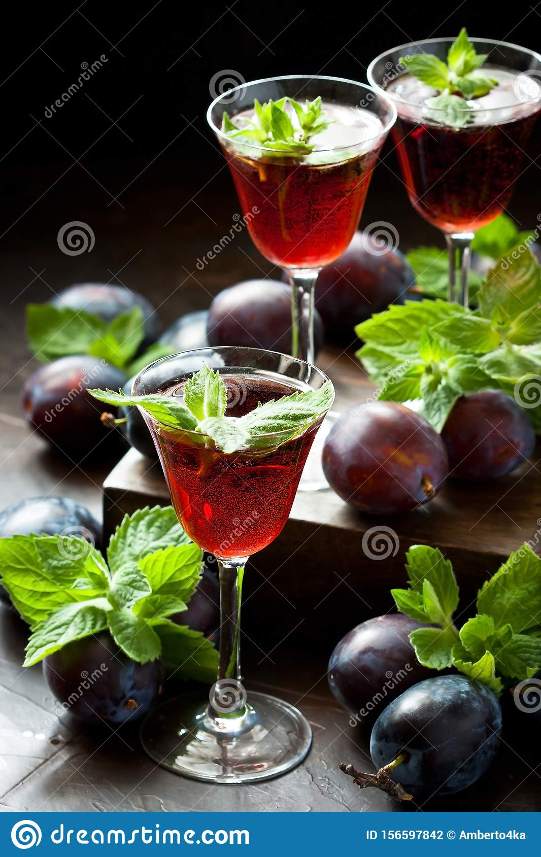 Glasses of fruit liqueur on dark background