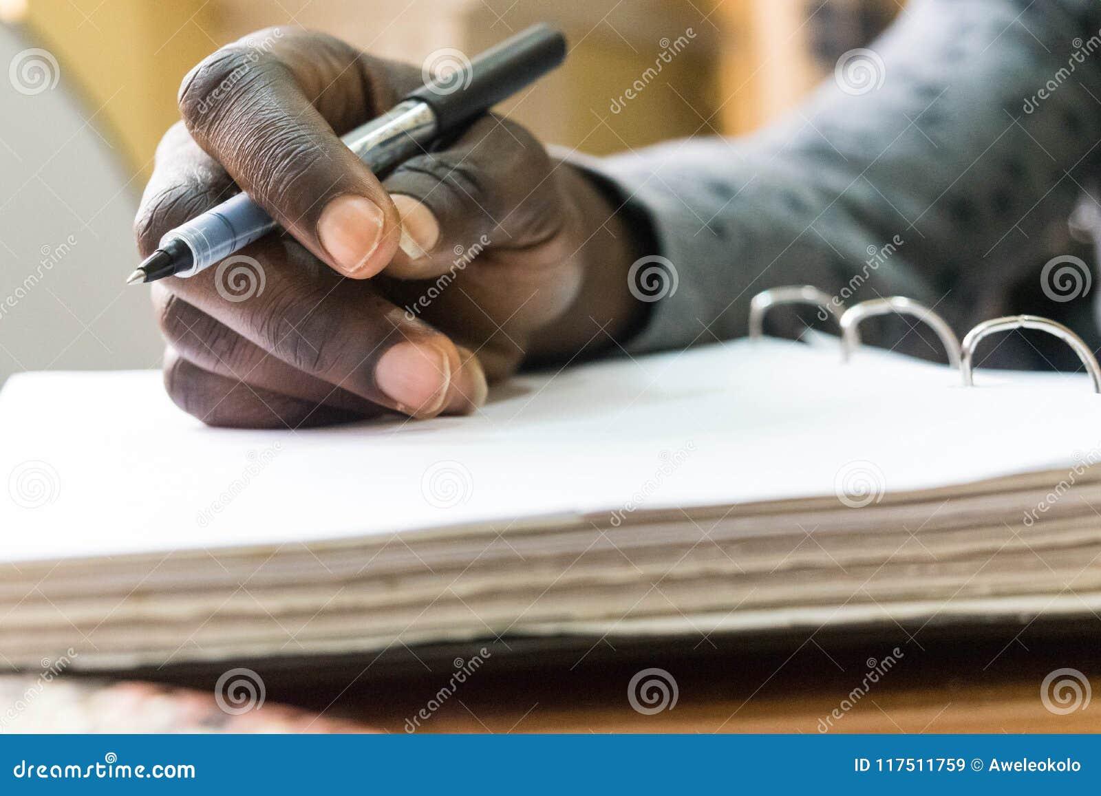Pluma de tenencia africana del hombre a disposición a escribir en el Libro Blanco en blanco