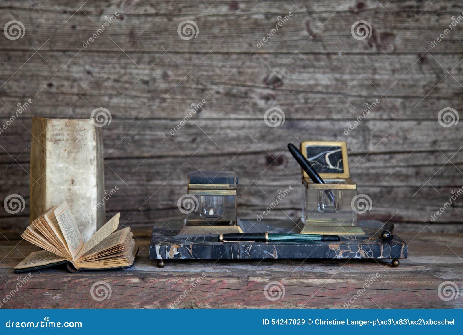 Pluma y libros viejos en Weathered de madera