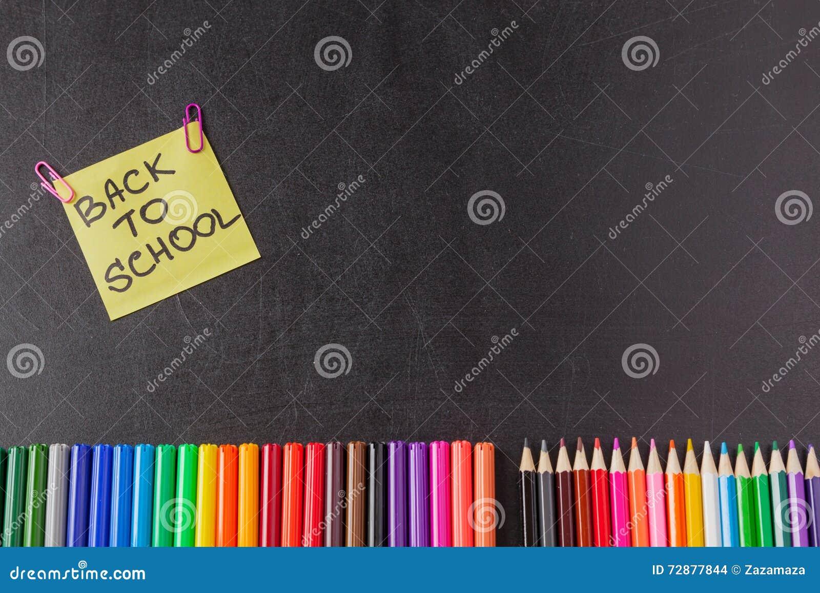 Plumas, lápices y título coloridos de nuevo a la escuela escrita en trozo de papel en la pizarra negra