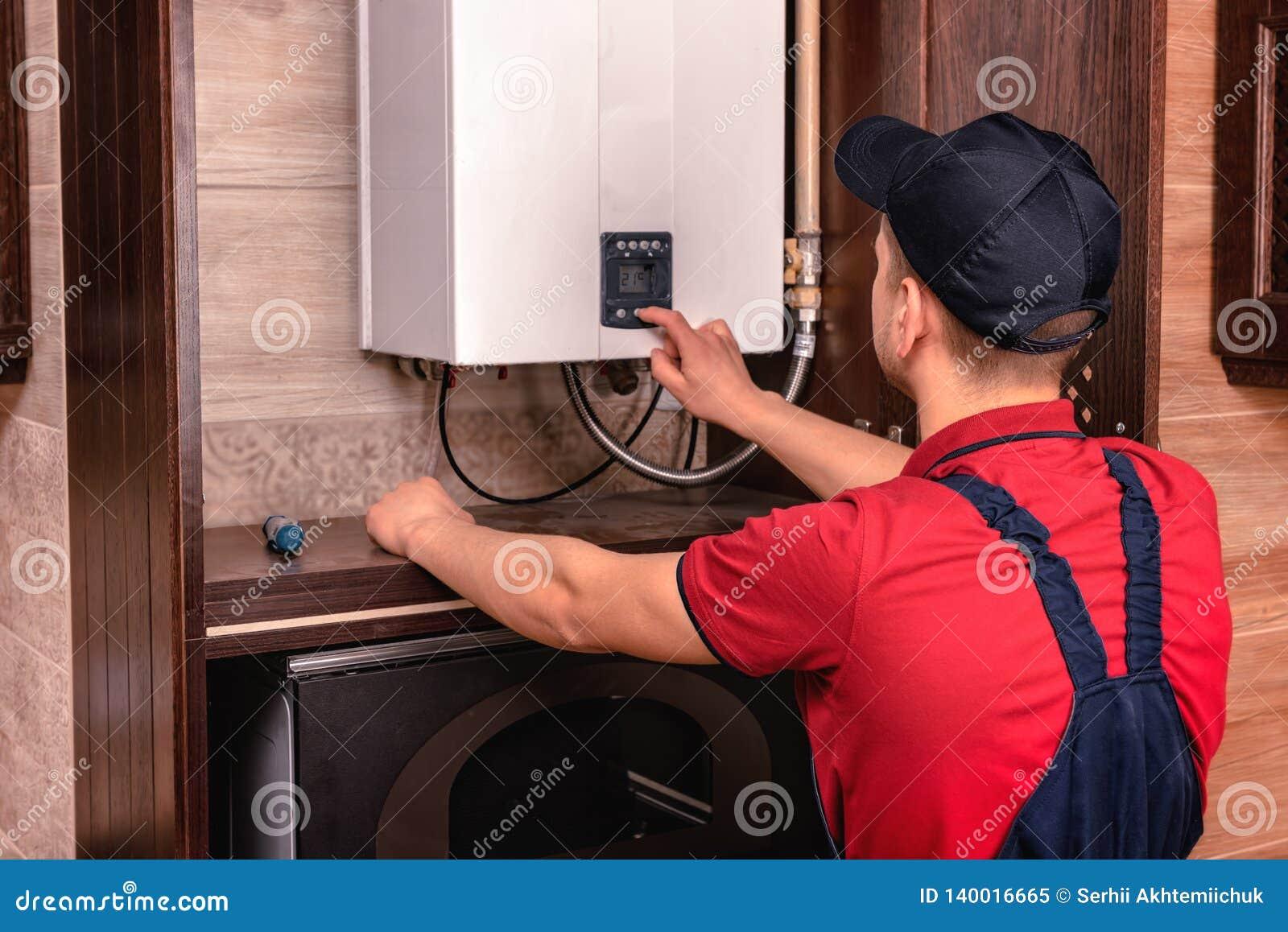 Plumber adjusts gas boiler before operating