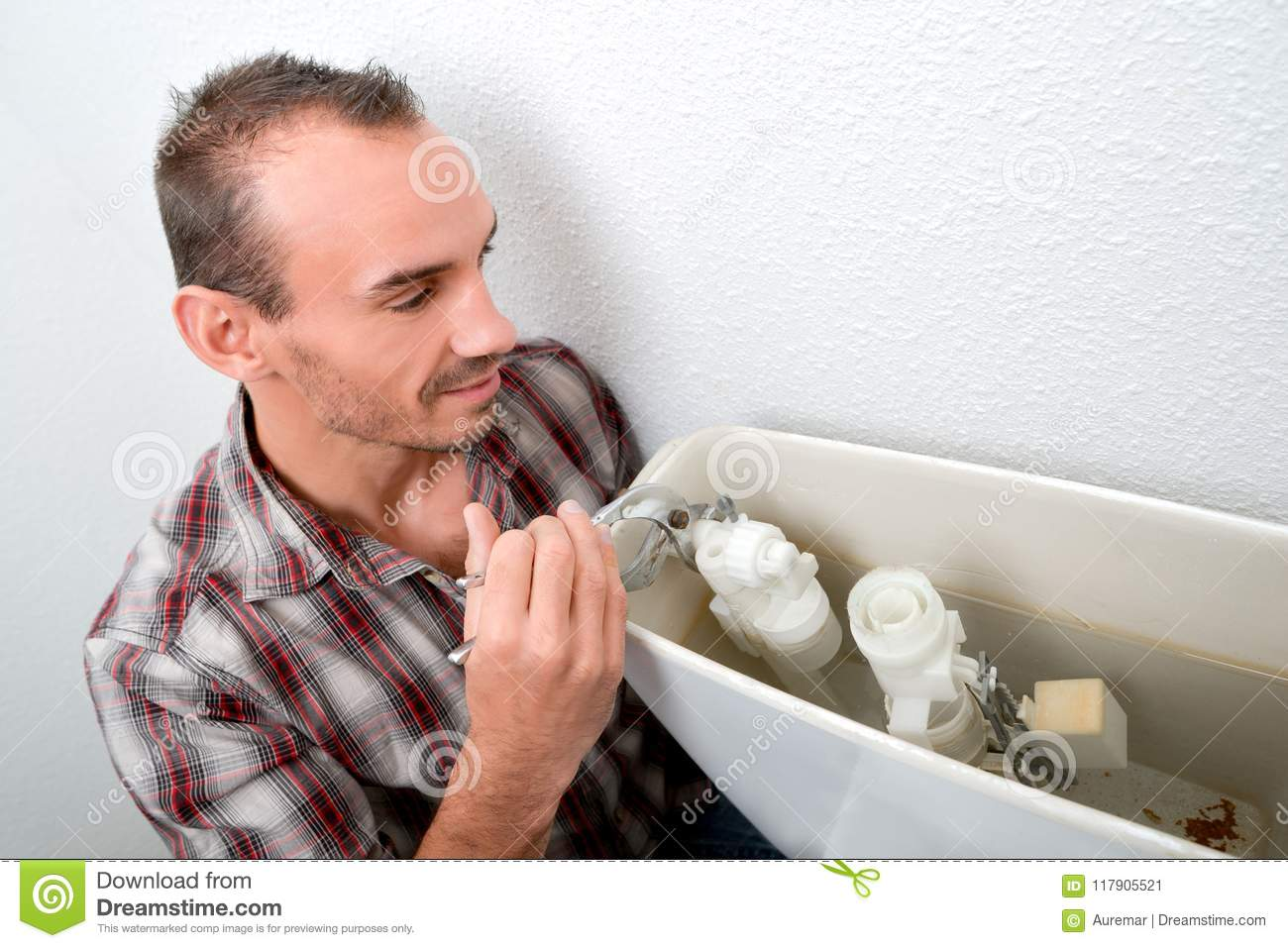 Plumber fixing a toilet stock image. Image of professional - 117905521