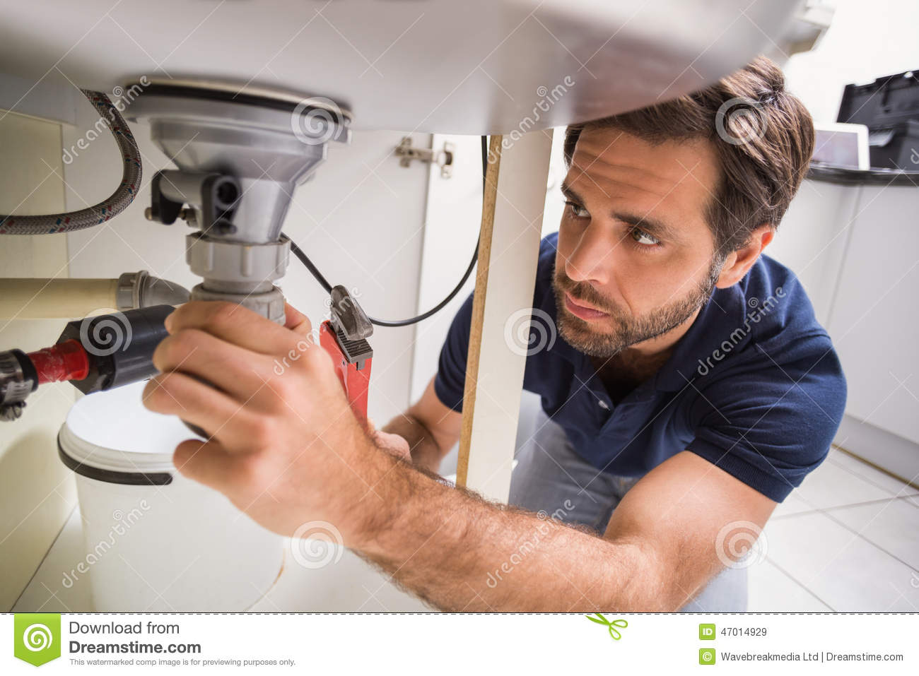 plumber-fixing-under-sink-kitchen-47014929.jpg
