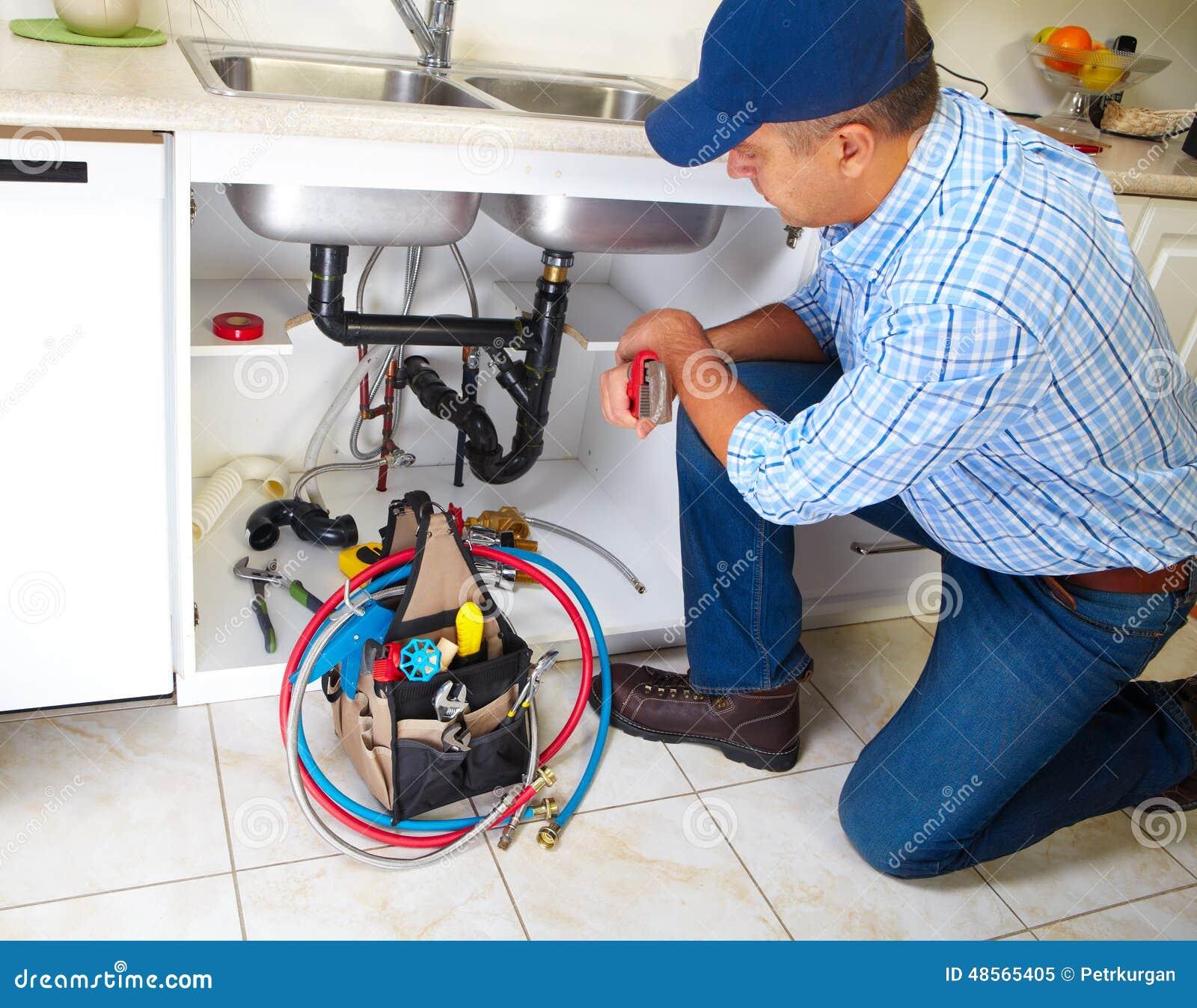 Kitchen Renovation Online Tool: Plumber On The Kitchen. Stock Photo