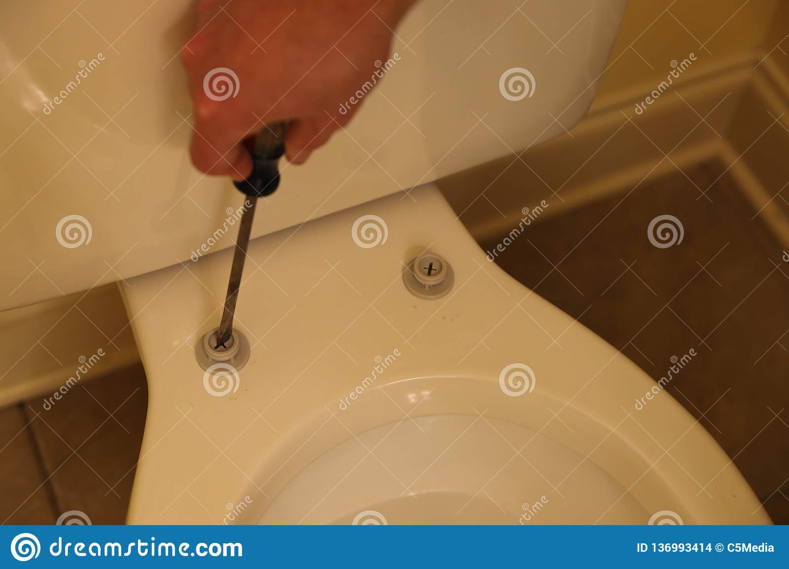 Plumber repairing toilet seat. Plumber installing screws to replace new seat on toilet in home bathroom stock images