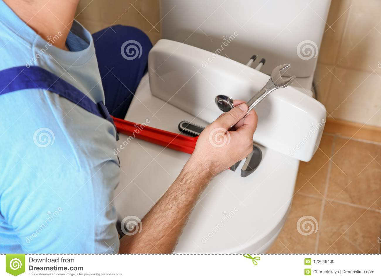 Plumber repairing toilet with wrench indoors