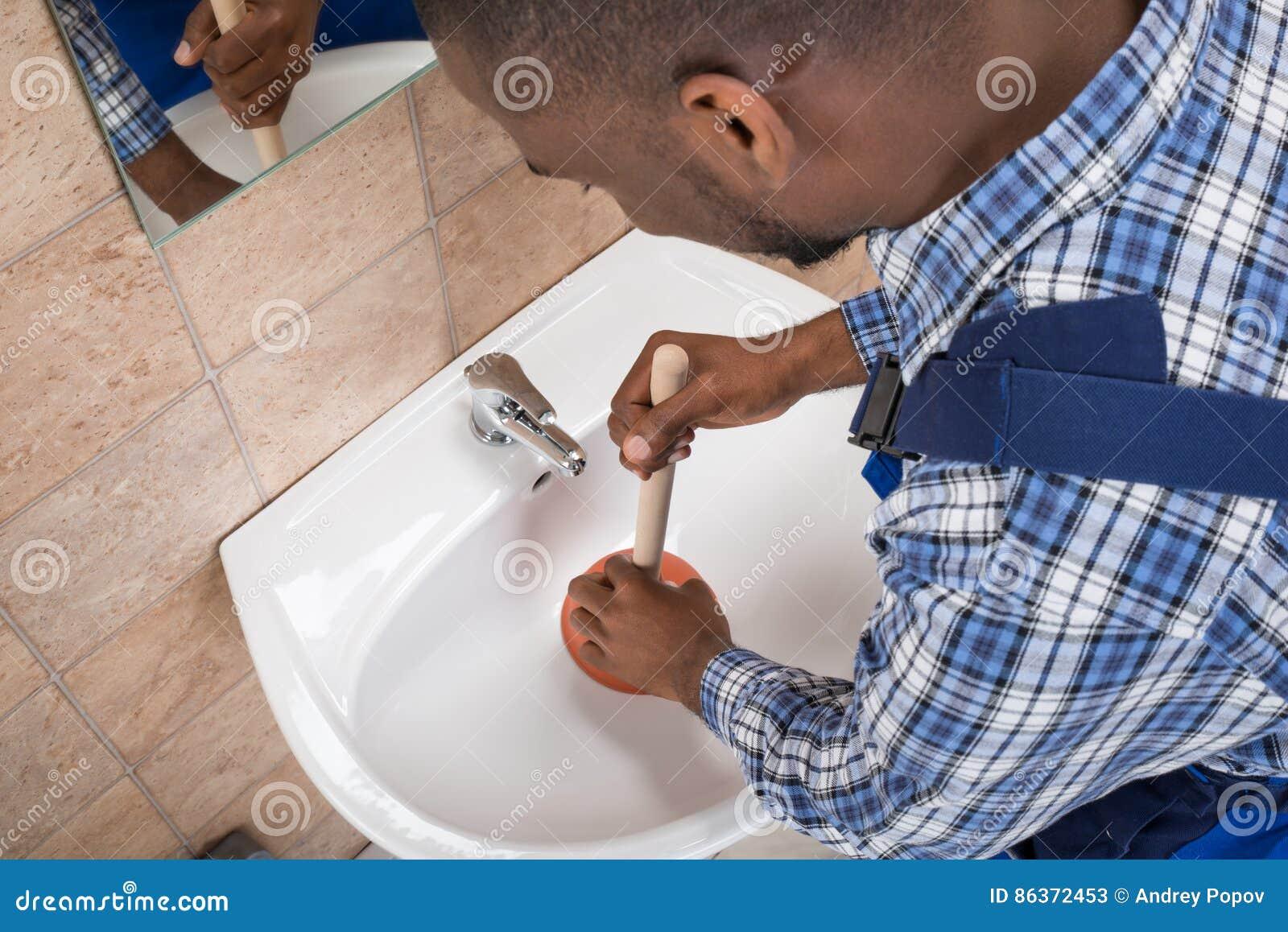 Plumber`s Hand Using Plunger In Bathroom Sink