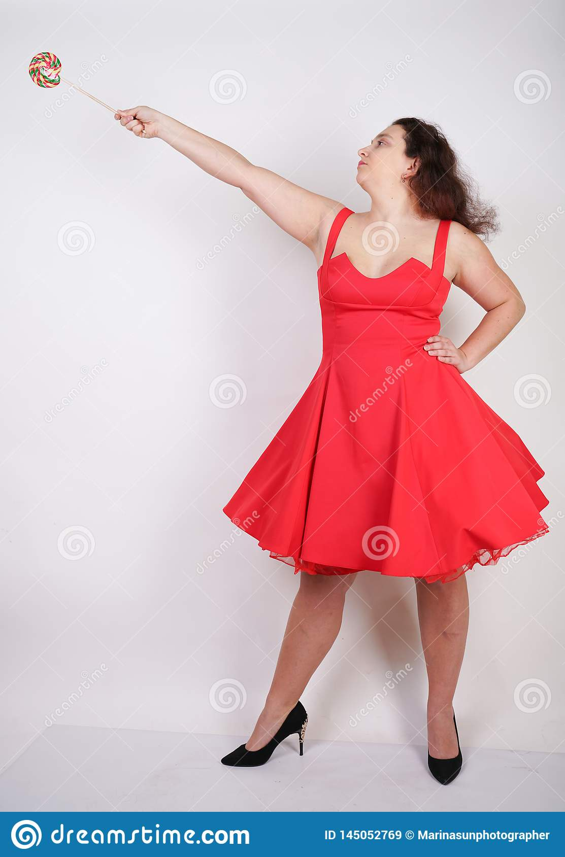 Plump woman in a red pinup dress. chubby fashionable girl standing on white background in Studio