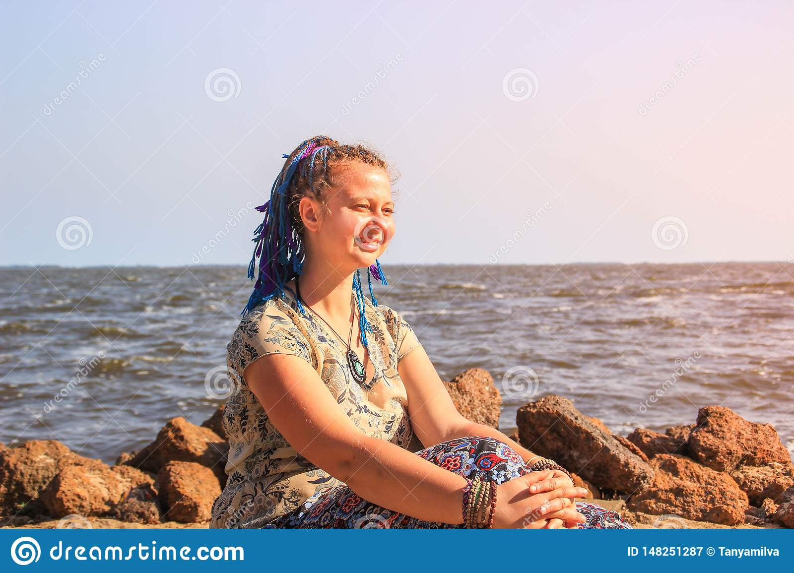 A plump young white girl traveler with blue pigtail hair sits barefoot on the sand against the backdrop of Lake Victoria