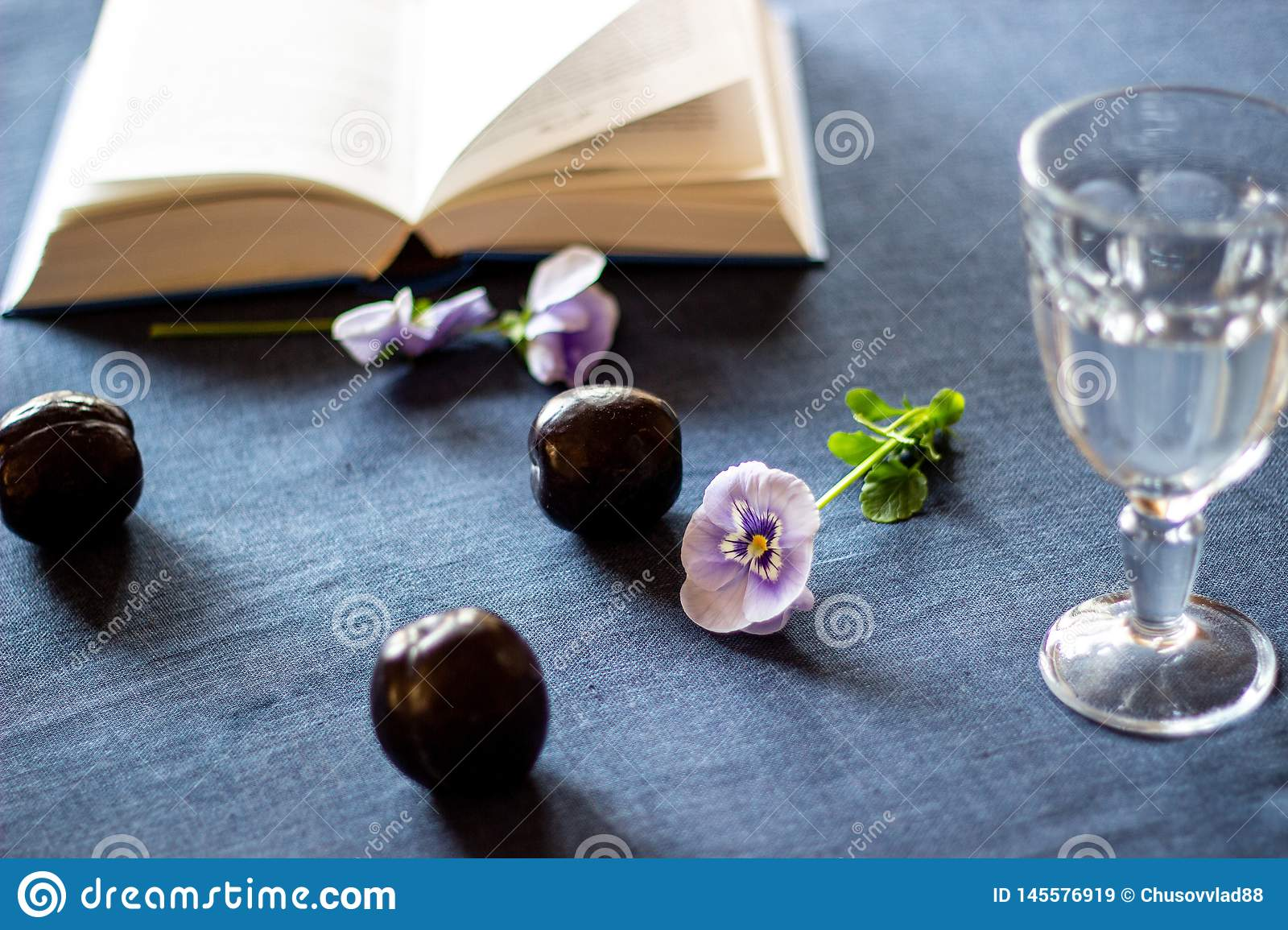 Plums, flowers, a book and a glass of water on a blue background