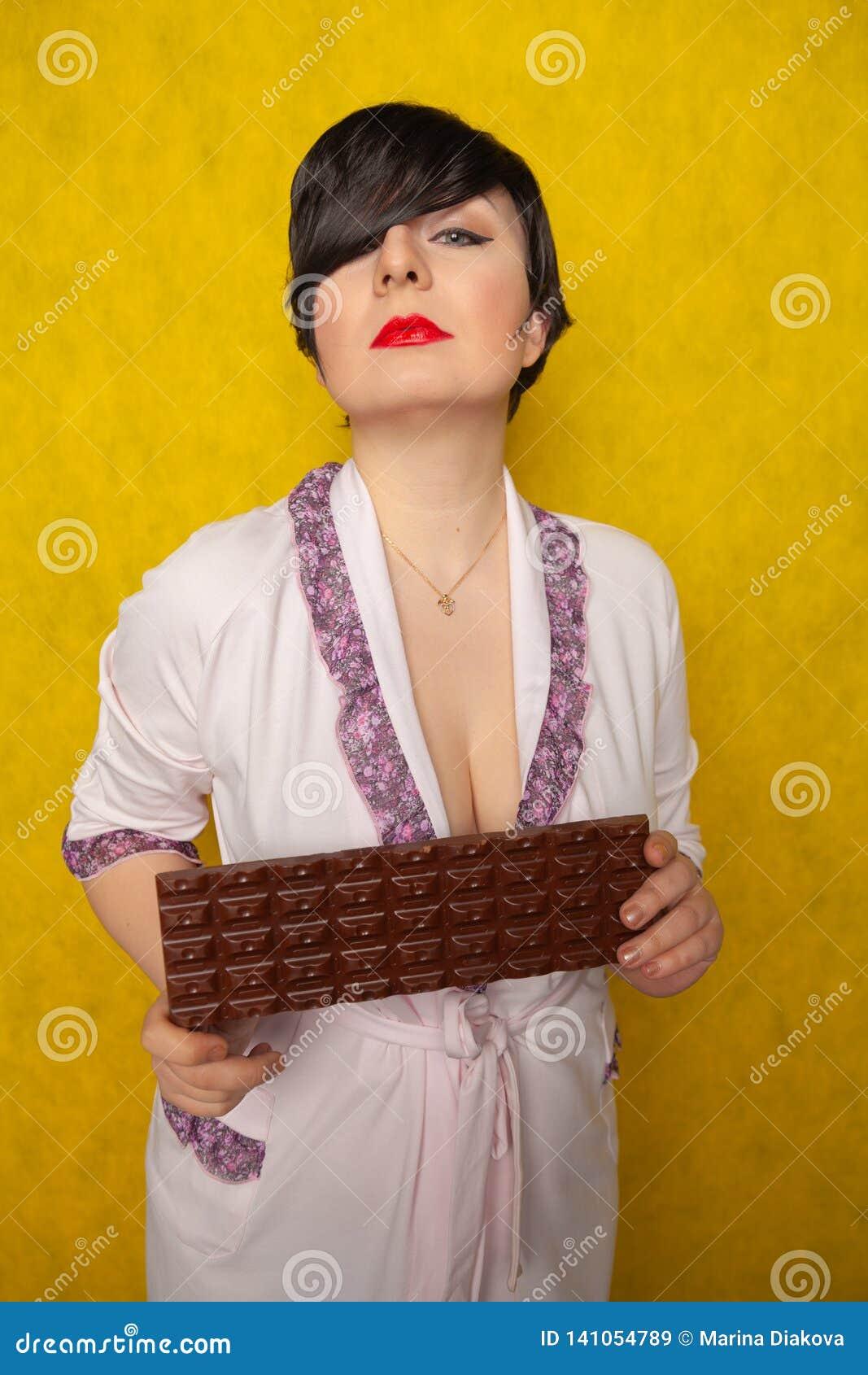 Plus format står kvinnan, i en rosa badrock och att rymma i hennes händer en enorm stång av choklad på gul bakgrund