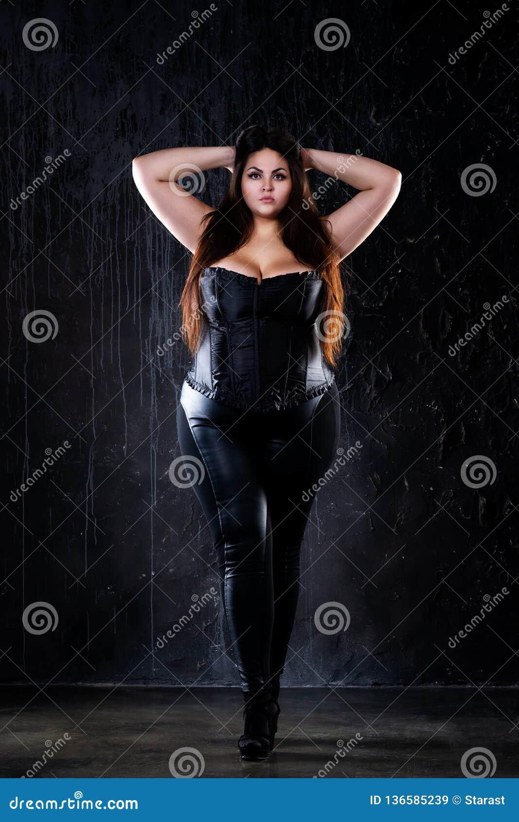 Plus formatmodemodell i sexig kläder fet kvinna på svart bakgrund, överviktig kvinnlig kropp