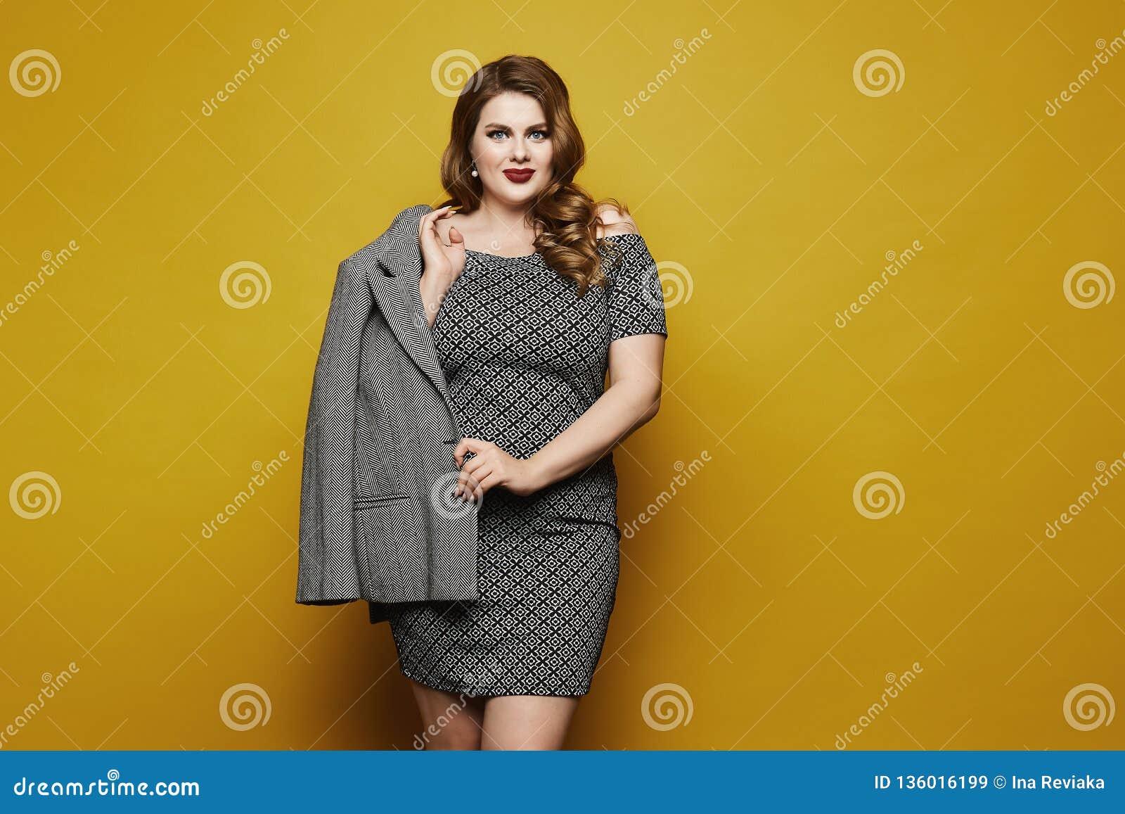 Plus sexig modellflicka för format, trendig blondin med ljus makeup och med den stilfulla frisyren i klänningen med geometriskt